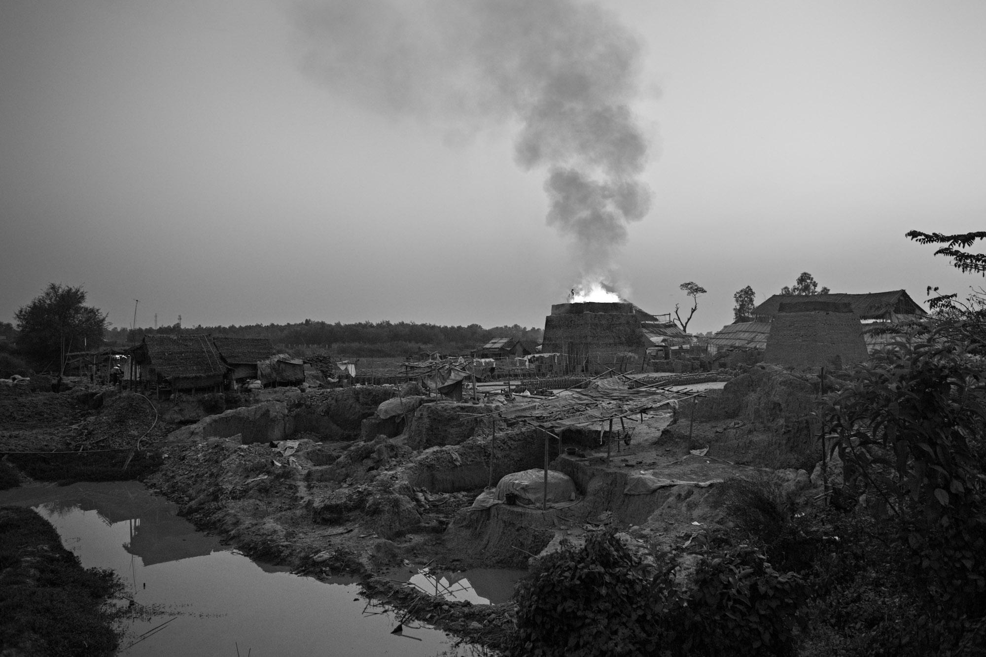 Fire and smoke from a brick kiln burns into the dusk.