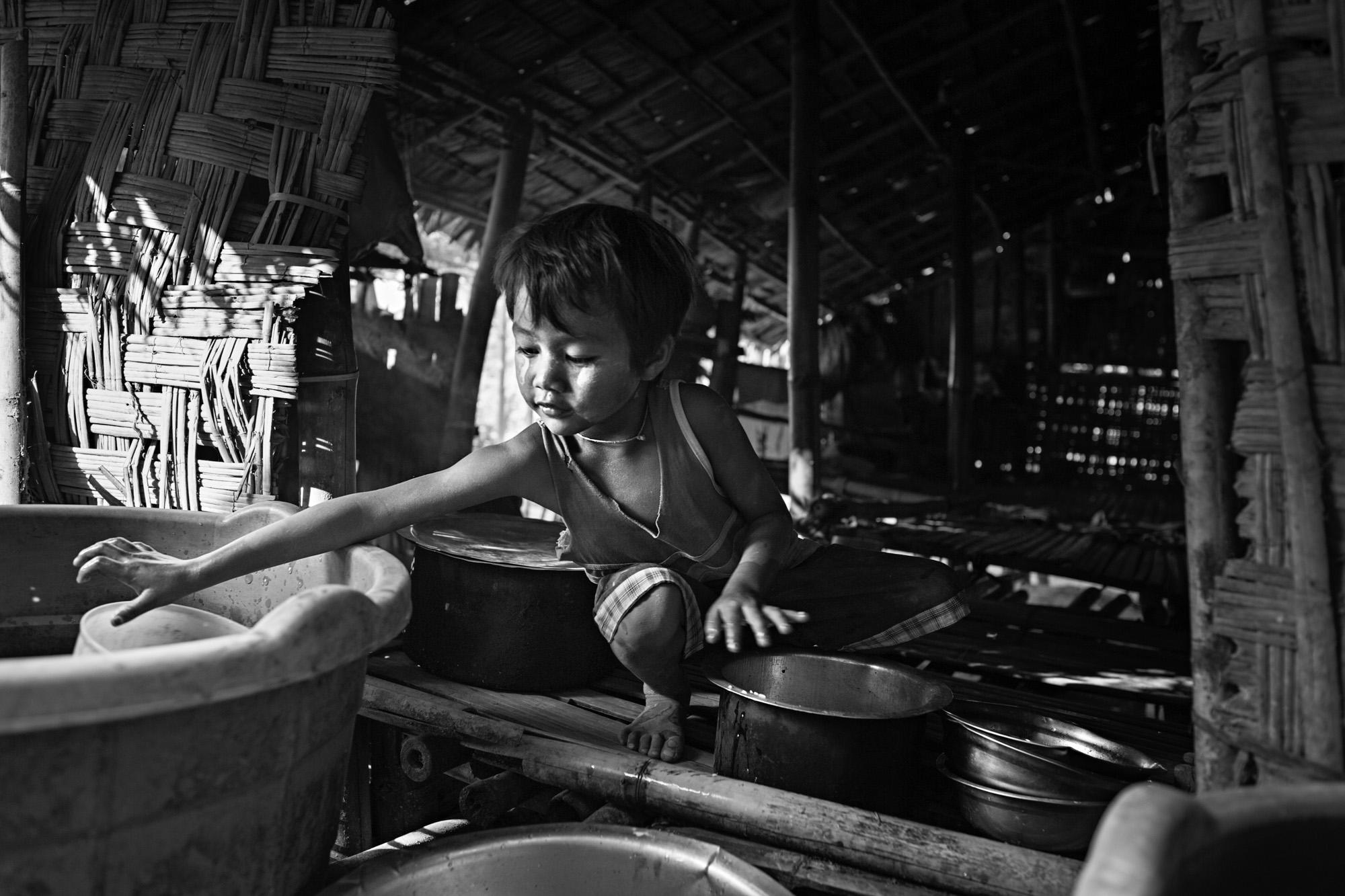 Saung Nin Wai cleans dishes after dinner.