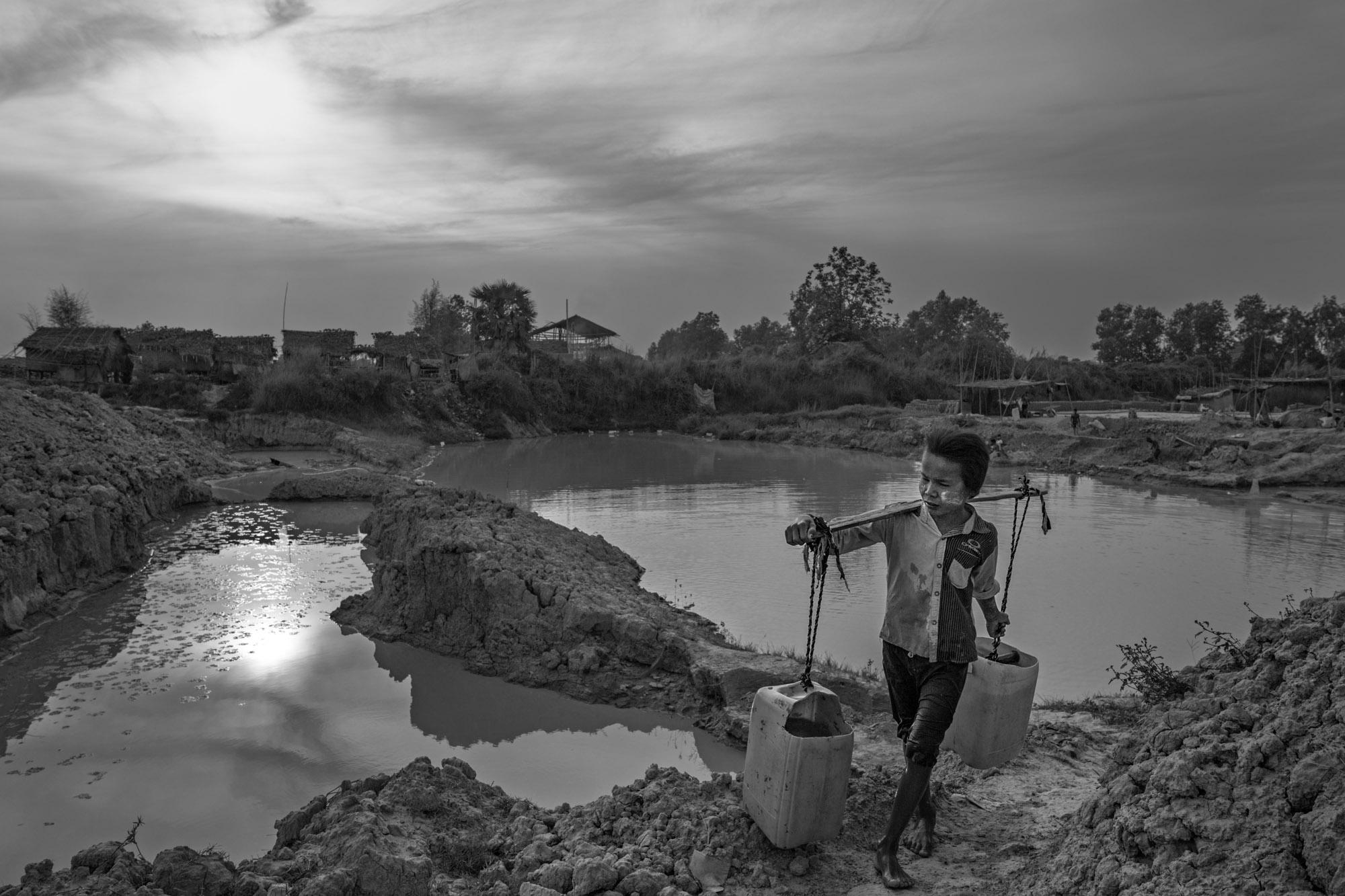Naing Lin Oo carries water from a machine-made pool to their brick making station to moisten the clay.