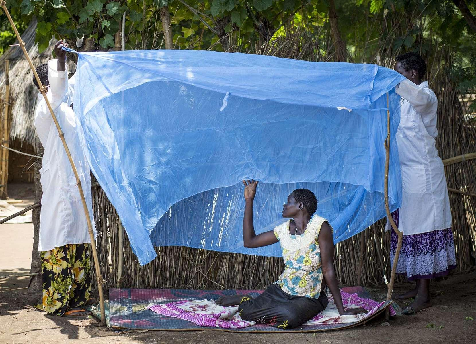 With the help of a pregnant woman, health extension workers Achang Objo, left, and Abang Obang, give a live demonstration of the proper use of mosquito net to the residents of Itang Woreda in Gambella State of Ethiopia, 29 August 2013.