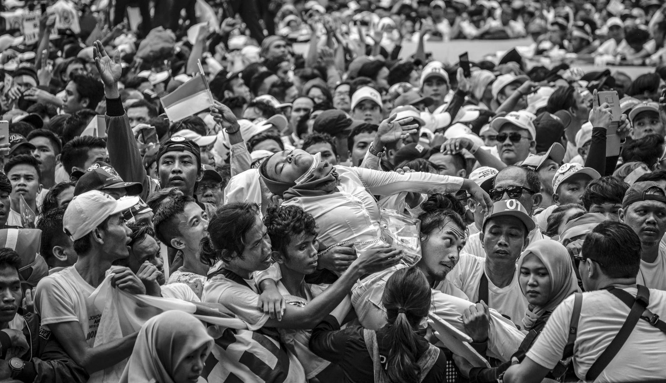 An unconscious woman suffering from heat stroke is been carried out of the packed crowd at a campaign rally for Indonesia's incumbent presidential candidate Joko Widodo at Gelora Bung Karno stadium in Jakarta, Indonesia, April 13, 2019.