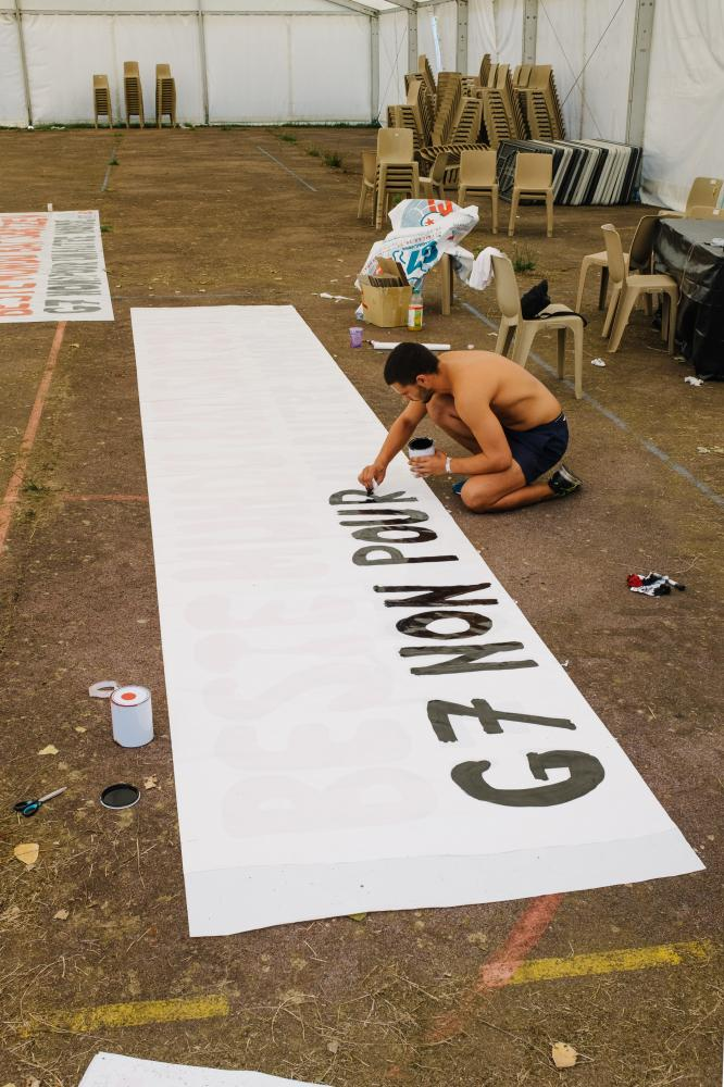 2019-08-23 - An activist paints a banner for upcoming demonstrations in the protest camp