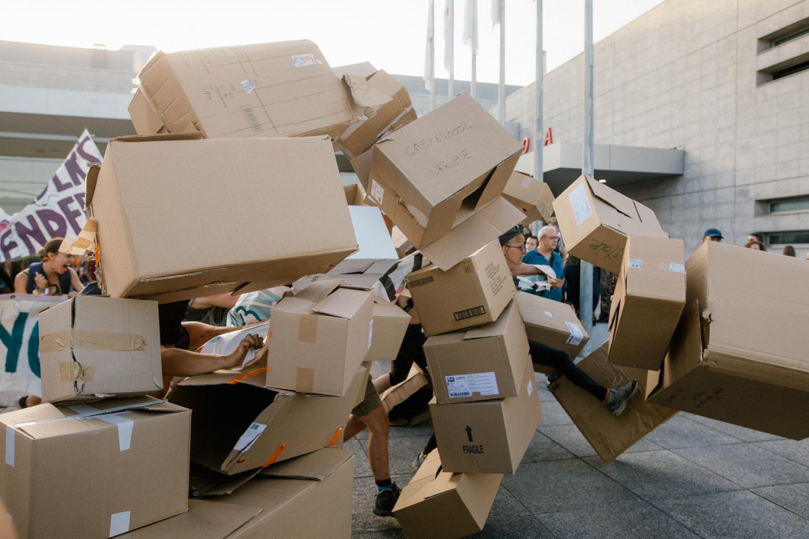2019-08-23 - Feminist activists rush through a wall of carton boxes with topics the group fights.