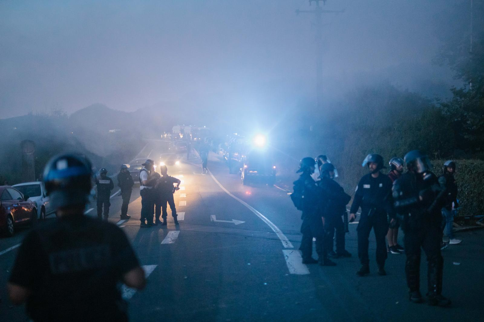 2019-08-23 - Police forces stand on road in front of protest camp, following clashes.