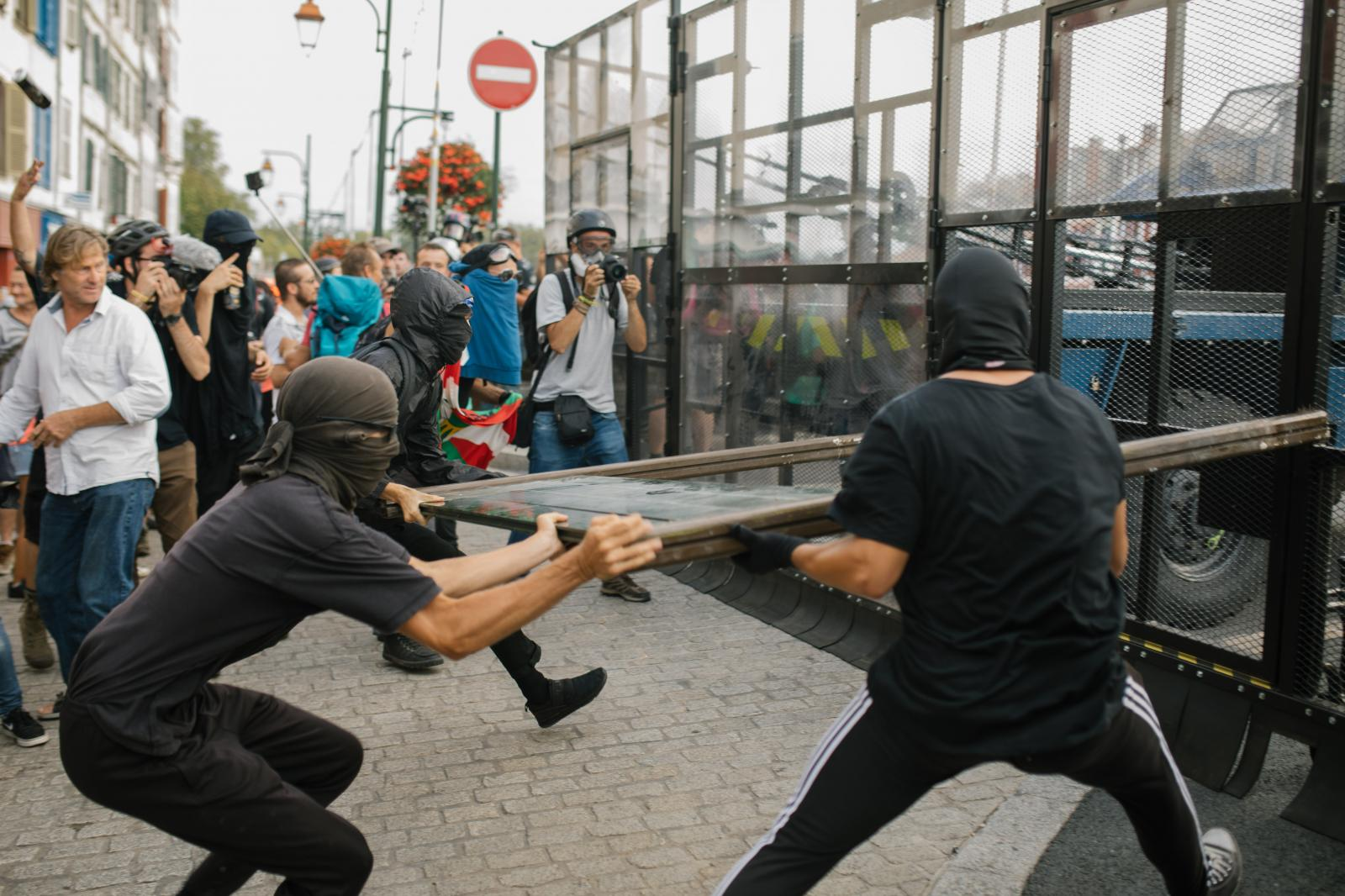 2019-08-24 - Activists ram a street sign into a police barrier on a bridge leading to Bayonne city center.