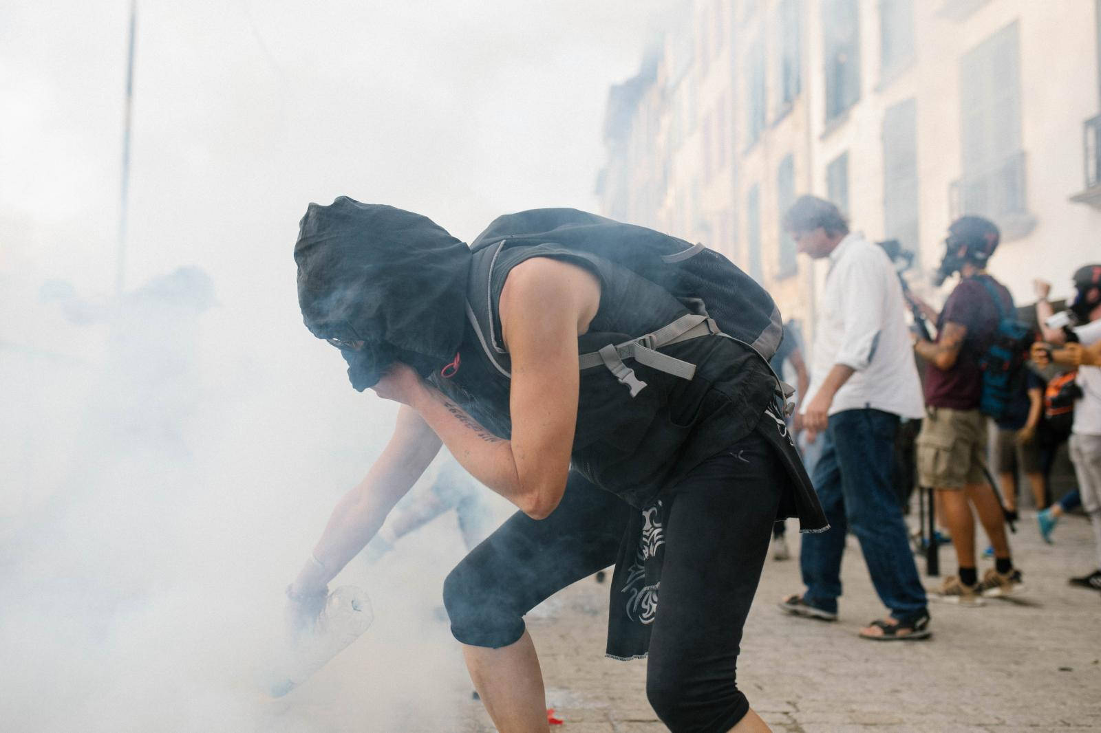 2019-08-24 - Protester extinguishes tear-gas fired by police.
