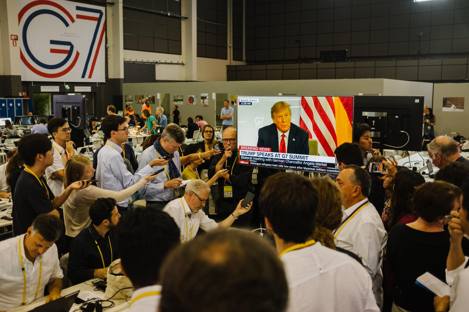 2019-08-26 - Journalists in the press center watch American president Donald Trump speak with press, during bilateral talk with german chancellor Angela Merkel.