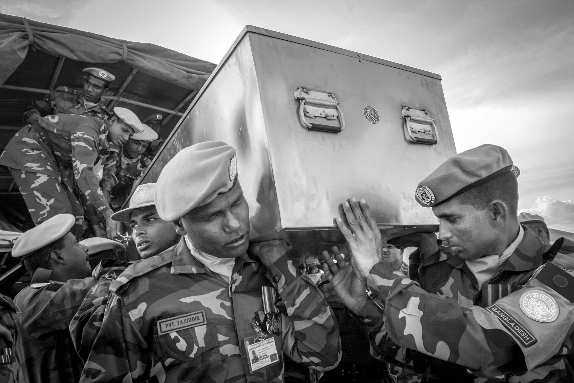 A body of Bangladeshi soldier killed in an ambush near Bunia  by a militia group is carried out of a truck to be returned to his home country.