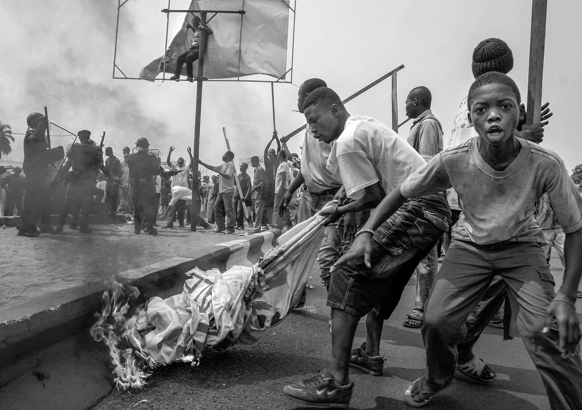 Supporters of UDPS, an opposition party which boycotted the election, burn campaign posters of candidates on the streets of Kinshasa, DR Congo.