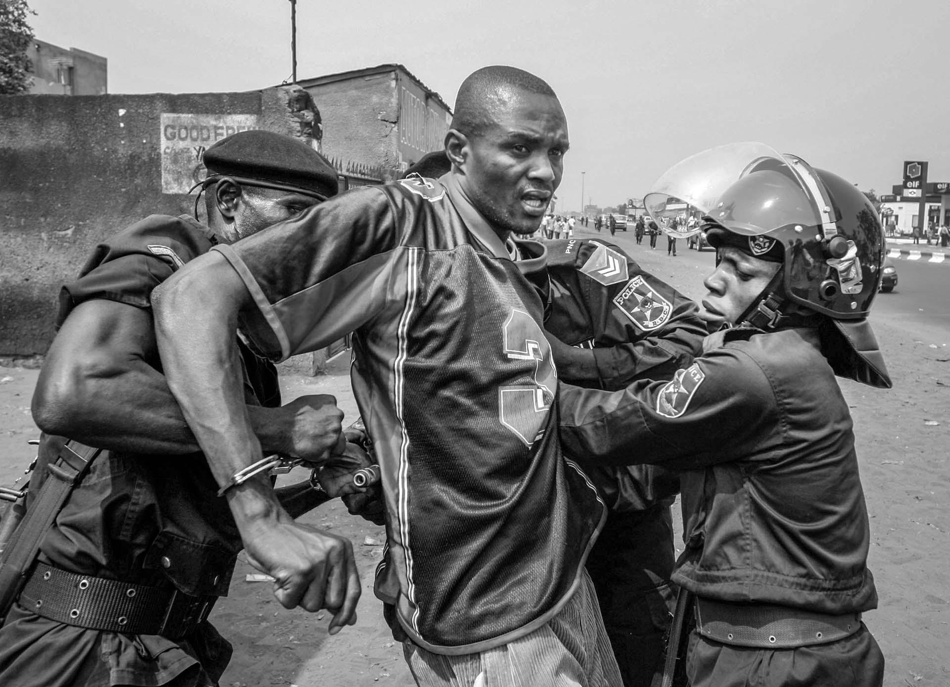 Riot police arrest a supporter of UDPS, Congo's main opposition party which boycotted the upcoming Presidential and National election, on the street of Kinshasa, DR Congo on June 30, 2006, the nation's independence day.