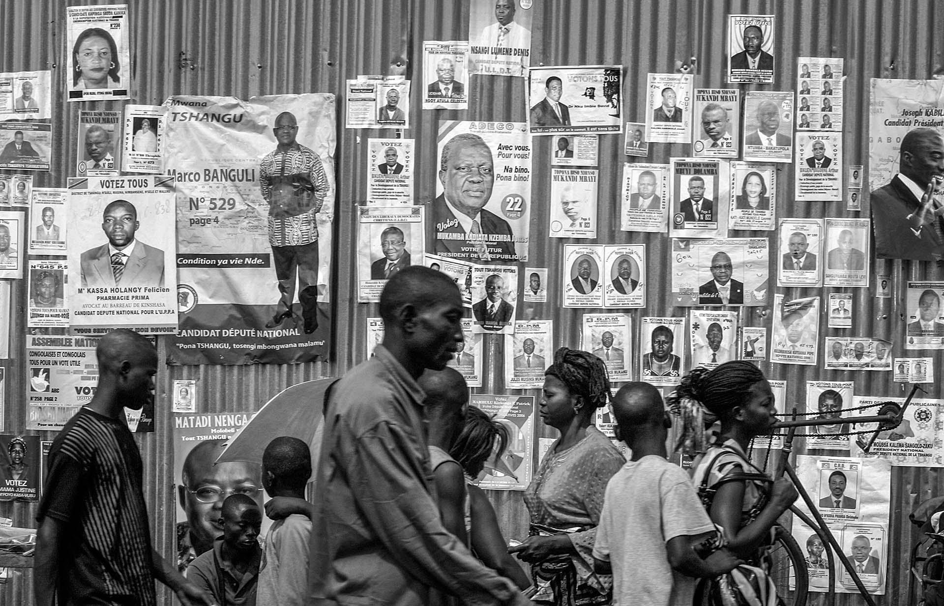 Posters of candidates for presidential and national elections occupy every inch of the wall in Kinshasa, July 25, 2006. There are 32 presidential candidate alone. As the presidential and national election draw near, the mood in the capital became tense. The war-torn Central African republic last had elections more than 40 years previously.