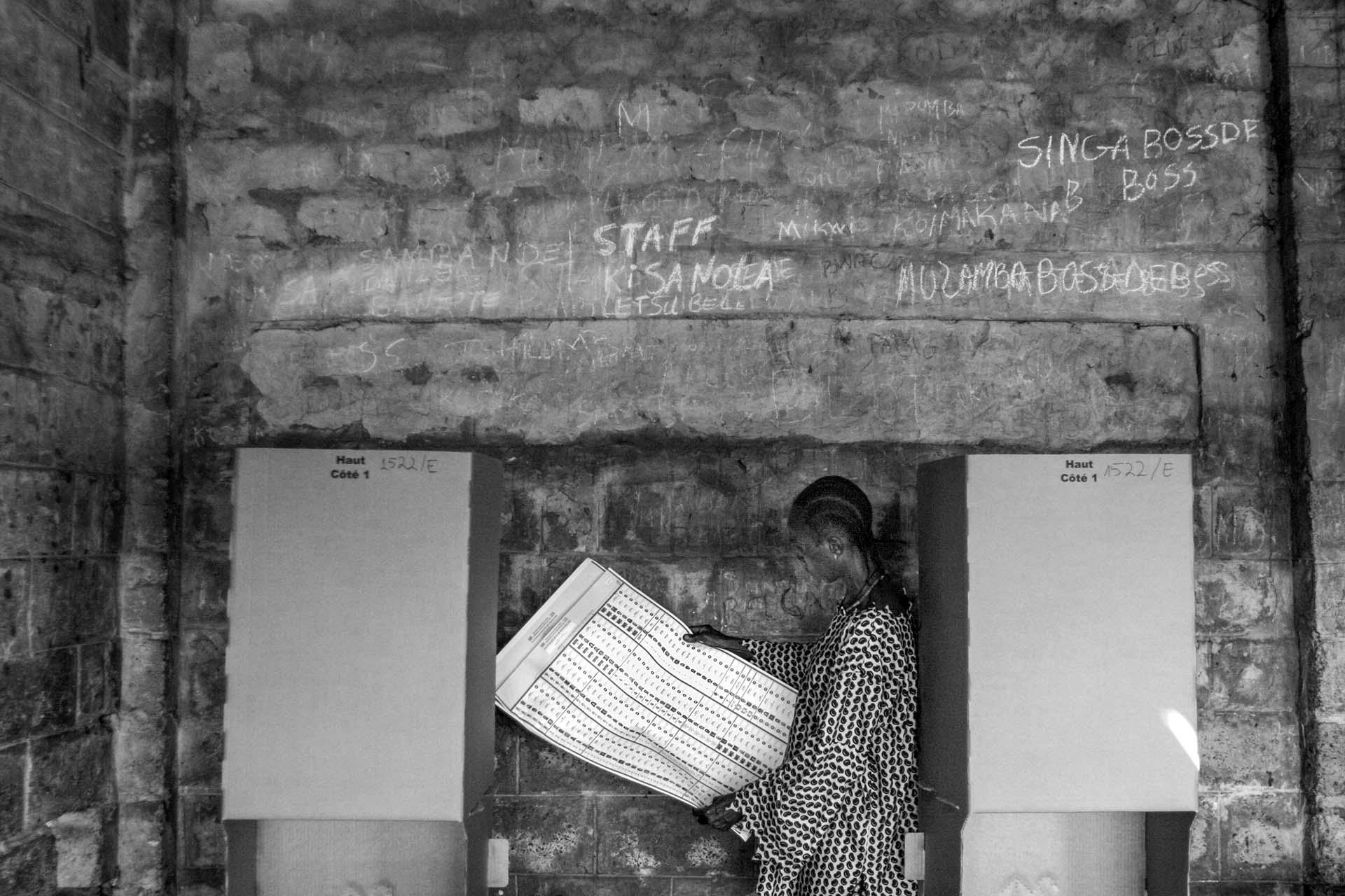 A Congolese man studies the 6-page ballot paper for legislative candidates at a polling station in Kinshasa.