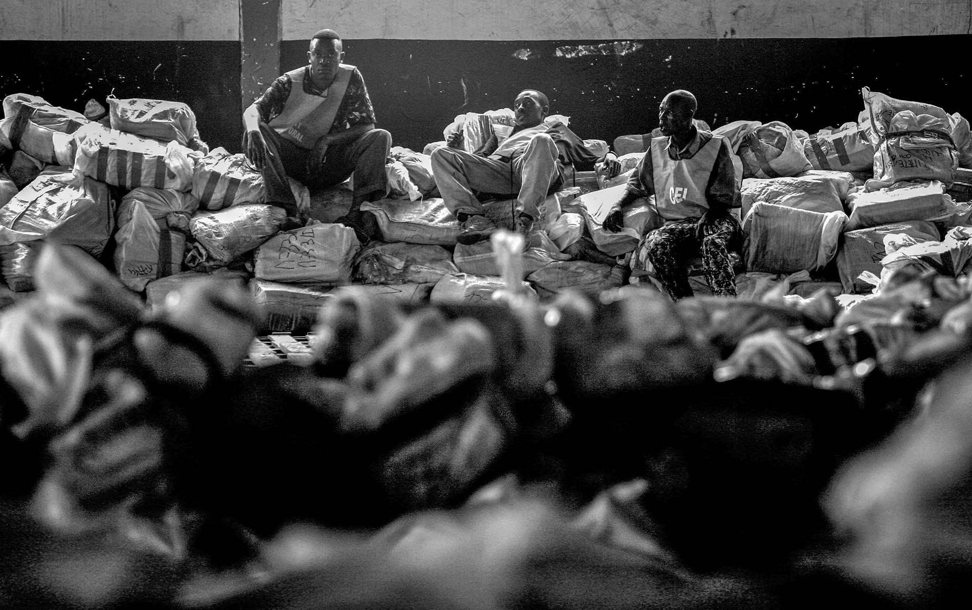 A tired electoral workers take a break from sorting ballots for counting and recorded at a heavily guarded storage facility in Kinshasa.