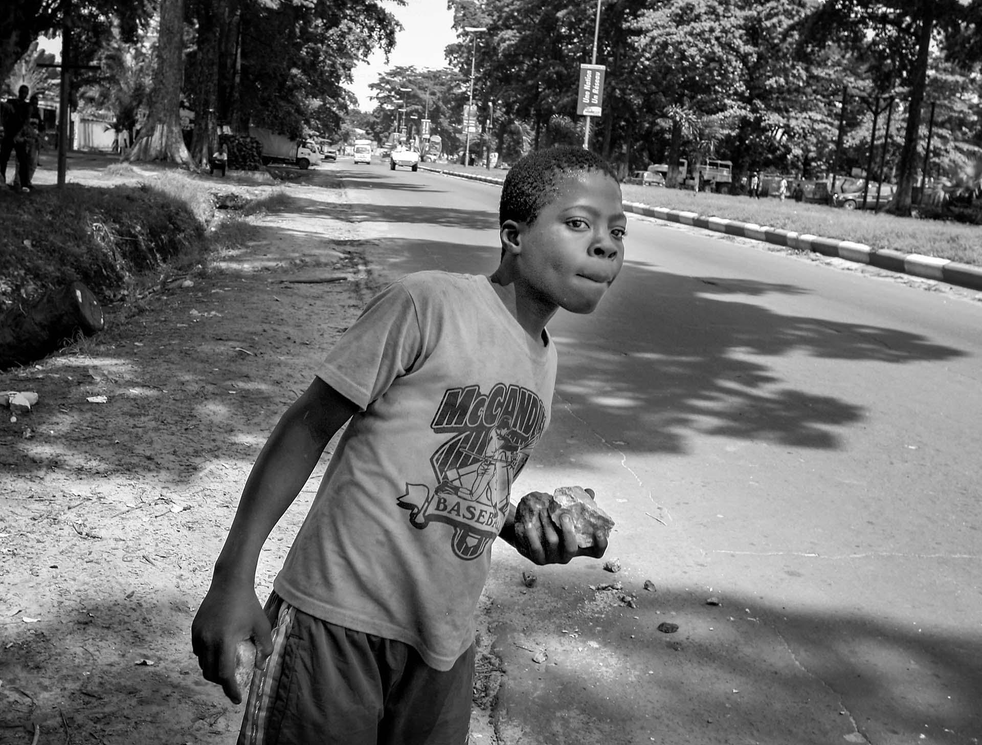 A Congolese youth looks for an opportunity to throw his rocks at police on the main street of Kinshasa. The day after Joseph Kabila was declared as the president, the air is tense in the capital.
