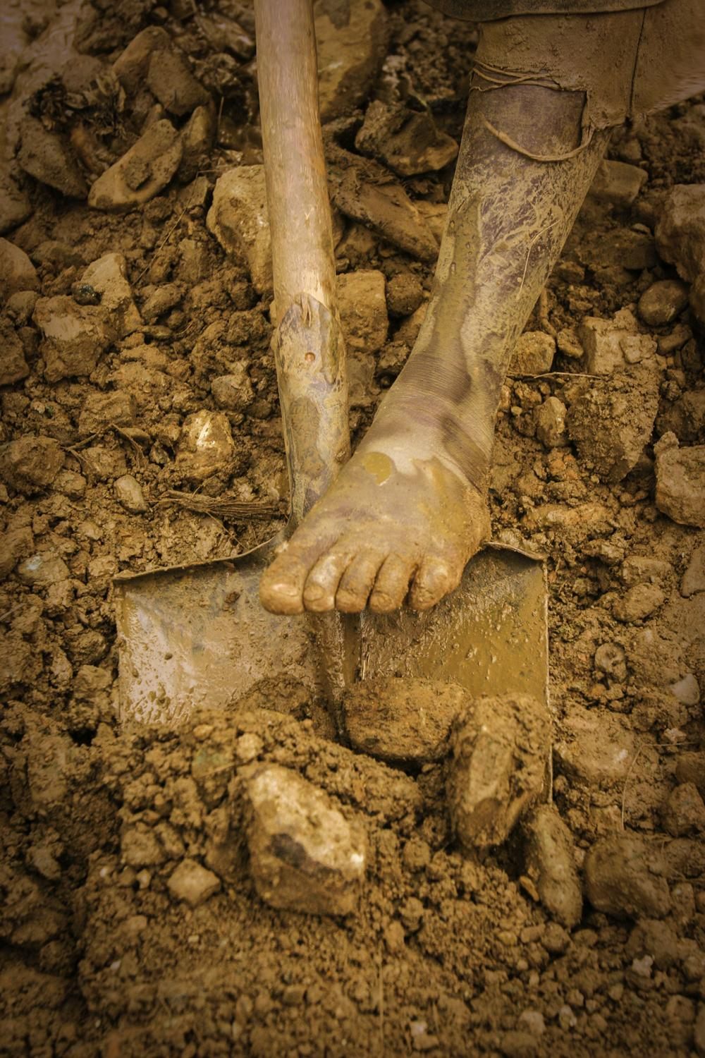 On hands and knees, mud and rocks is processed. Hardly any machinery is used to extract the gold in in most DR Congo mines.