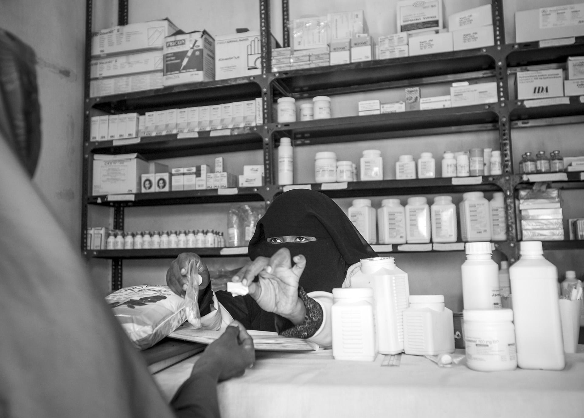 Somali nurse dispenses medicine to a newly arrived refugee from Somalia at a reception center in Maifa, Yemen.