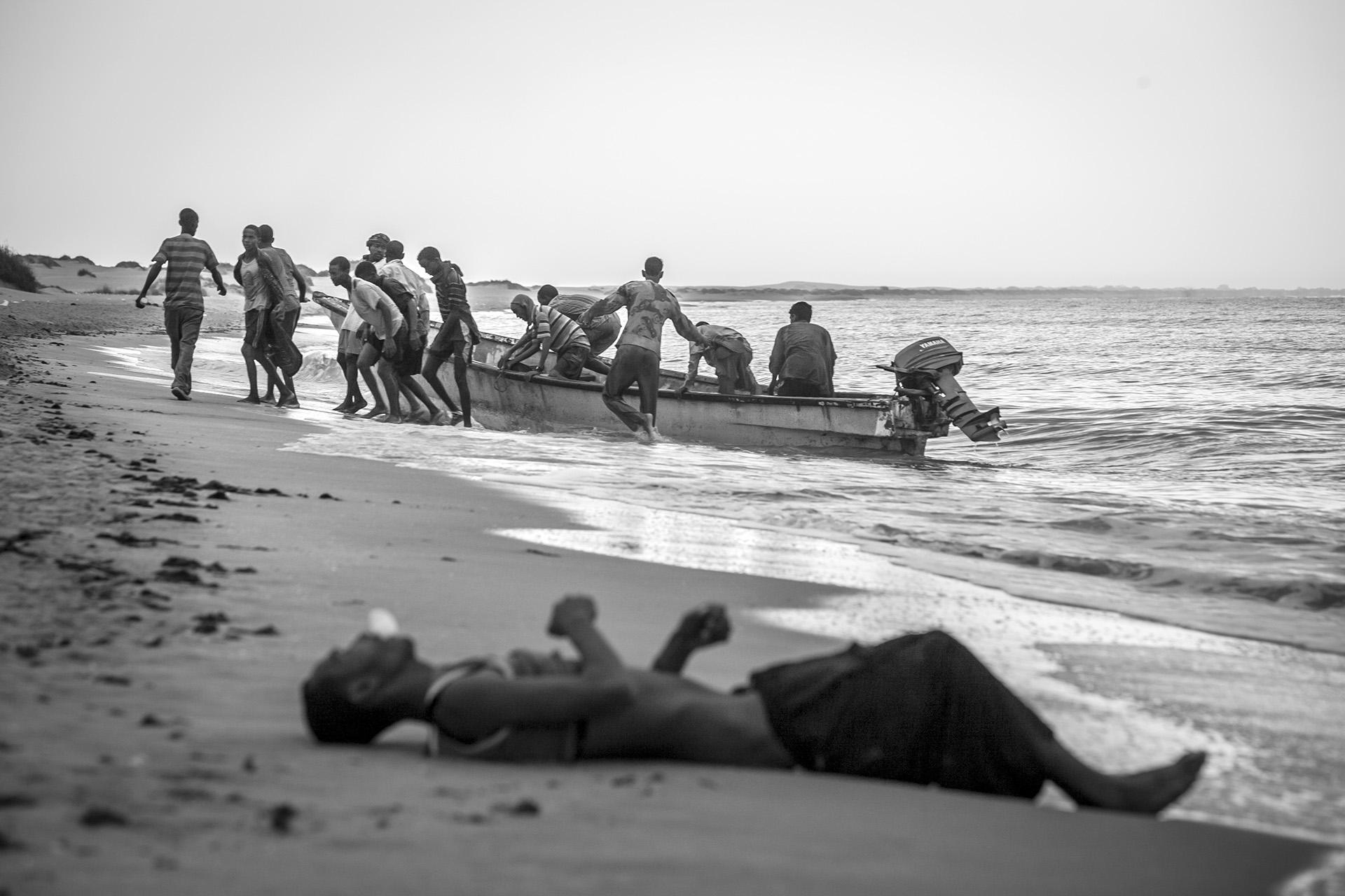 Refugees rescued by local fishermen are brought to a shore after being forced into the water far offshore. Like the victim in the foreground, many of their fellow passengers were not so lucky, lost their lives to the sea.