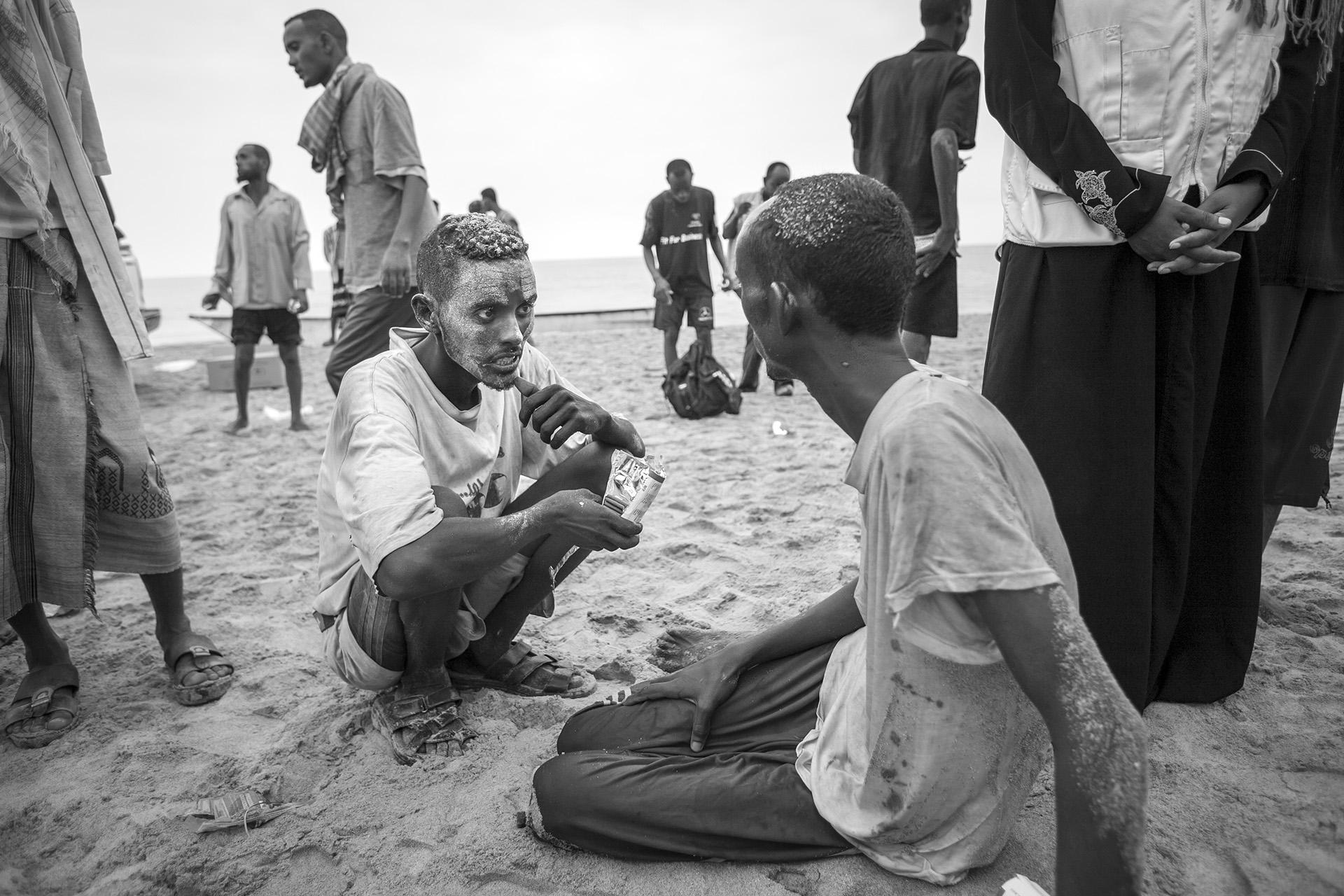 A Somali man offer his biscuit to another refugee at the beach after landing.