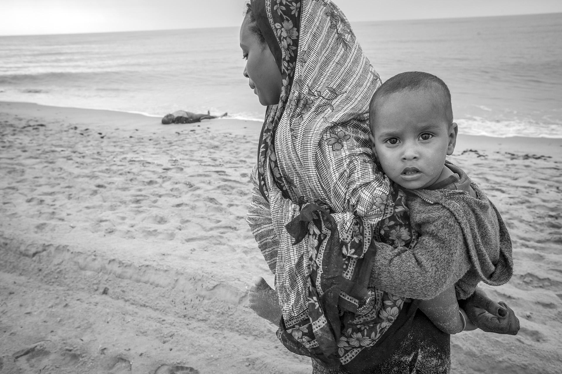 Fadua Ibrahim Haj Mohamed from Ethiopia walks along the beach she just reached in search of her older sister on December 1, 2008 near the town of Afwar on the Yemeni coast. She is carrying Riyadh Mukhter Sutlan, 1 year and 5 month old, the son of her missing sister. After exhausting the search, she believed that her sibling was dead, however Fozia Ahmed Hoshin, was rescued by fishermen and united with her family at a reception center.