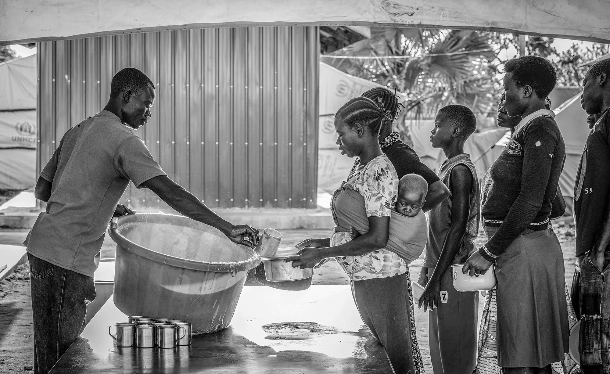 Refugees receive a hot meal at Kuluba Collection Center in Koboko District in Uganda on March 1, 2017.