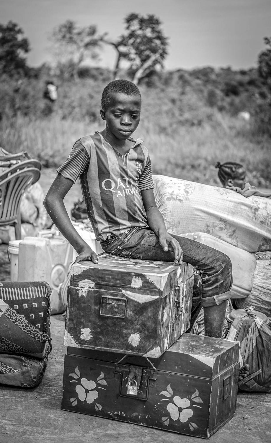 Conpijas Bida, 15, guards his family's belongings while waiting for the rest of his family to cross the border from South Sudan at Busia in Koboko district of Northern Uganda on May 1, 2017.