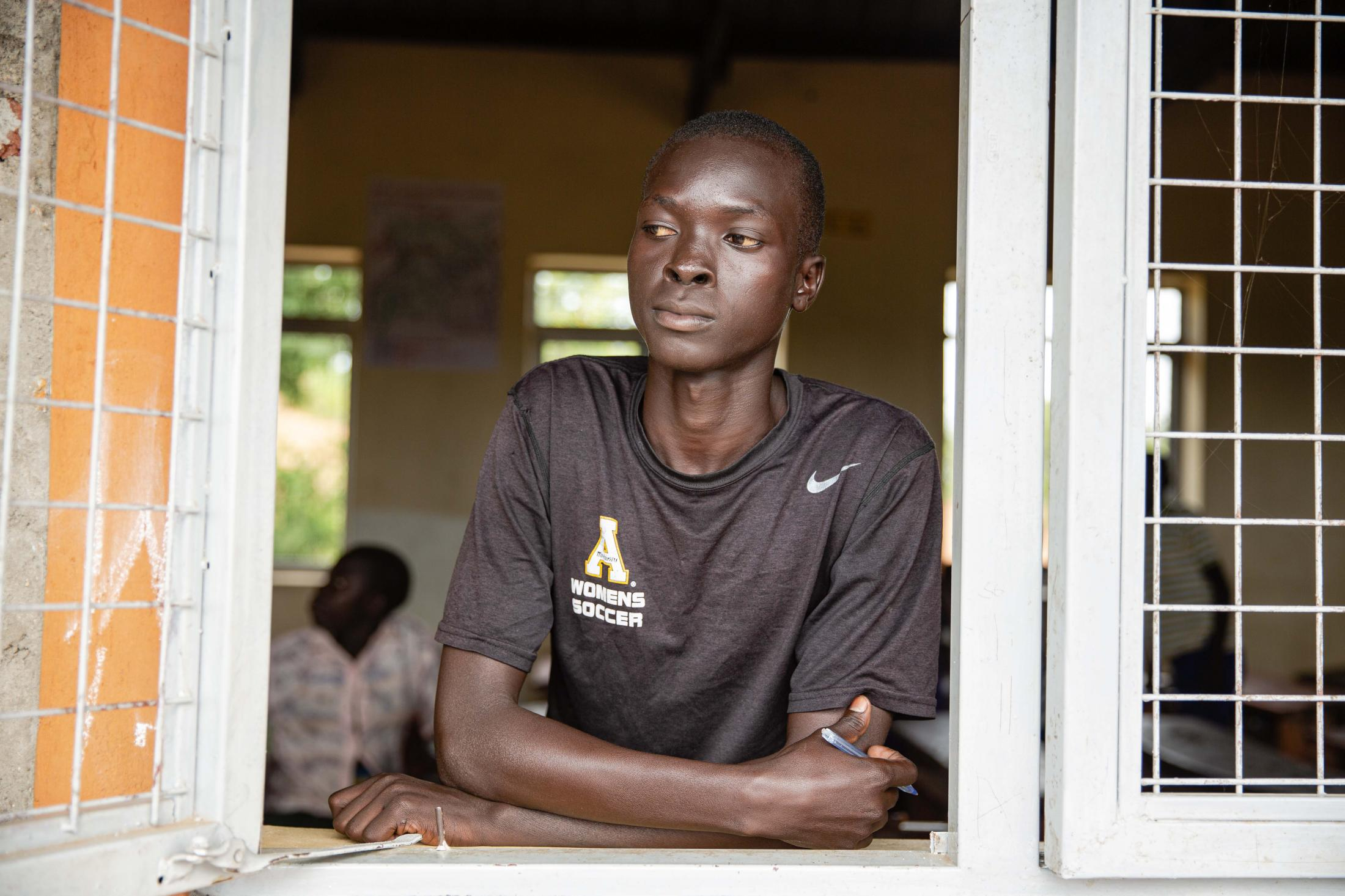 """Joseph Ladu, 15, joined Komgbe primary school under the Accelerated Learning Program in 2018 and is now in level 2. When war broke out in South Sudan in 2016, the family ran separately and he doesn't know if they're still alive or where they are. """"I now have good friends because of school."""" he says. For Norwegian Refugee Council."""
