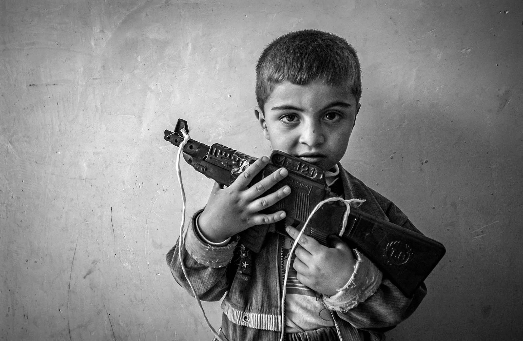4-year-old Bawan Ahmad Salih holds his toy AK-47 assault rifle at his uncle's house in border town of Kalar Monday, April 7, 2003. Real AKs and RPGs rest against a wall in their living room. Weapons of war are often seen in open at many household, children growing up