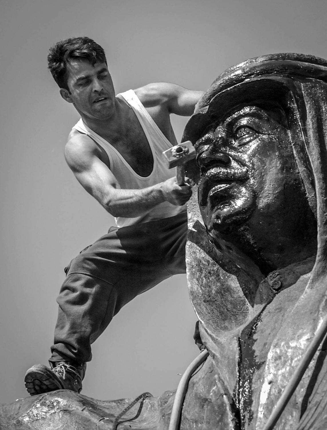 Kurdish man tries to smash the face of Saddam Hussein's statue on the day the City of Kirkuk fell.