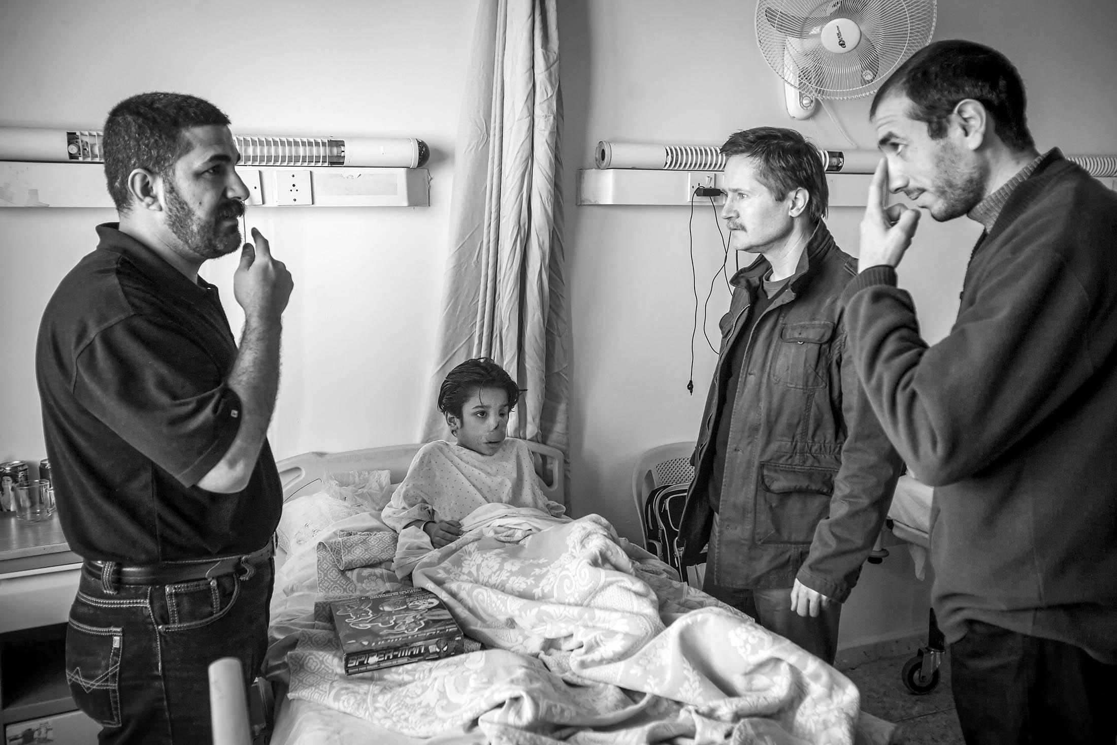 Dr. Andre Eckardt, a German surgeon flew in to help patients, consults with Abdullah and his father through an interpreter before surgery.