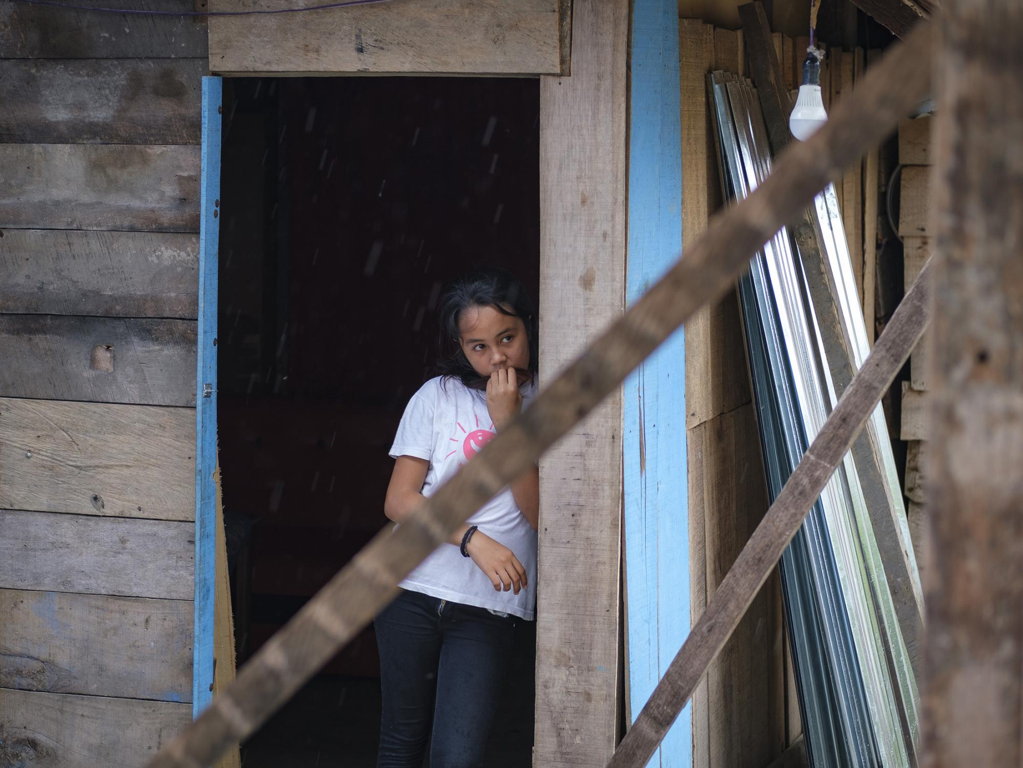 "Marzela, 12, watches the rain at her home in Donggala region, Central Sulawesi, Indonesia, February 25, 2019. With their house destroyed during 2018 earthquake, her family received a multi-purpose grant from Save the Children to rebuild their lives. ""We slept in the jungle for a month,"" said Marzela."