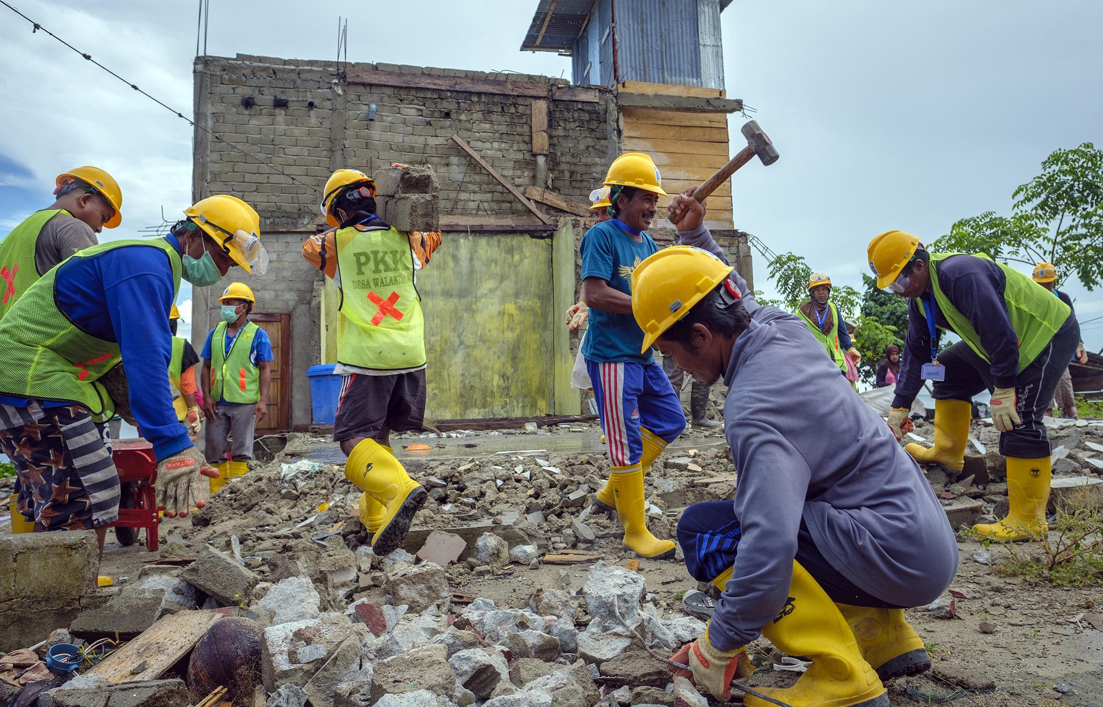 Debris from a collapsed building being removed next to a newly created Child Friendly Space built and supported by Save the Children Village in Walandanu in Donggala region, Central Sulawesi, Indonesia, February 25,  2019.