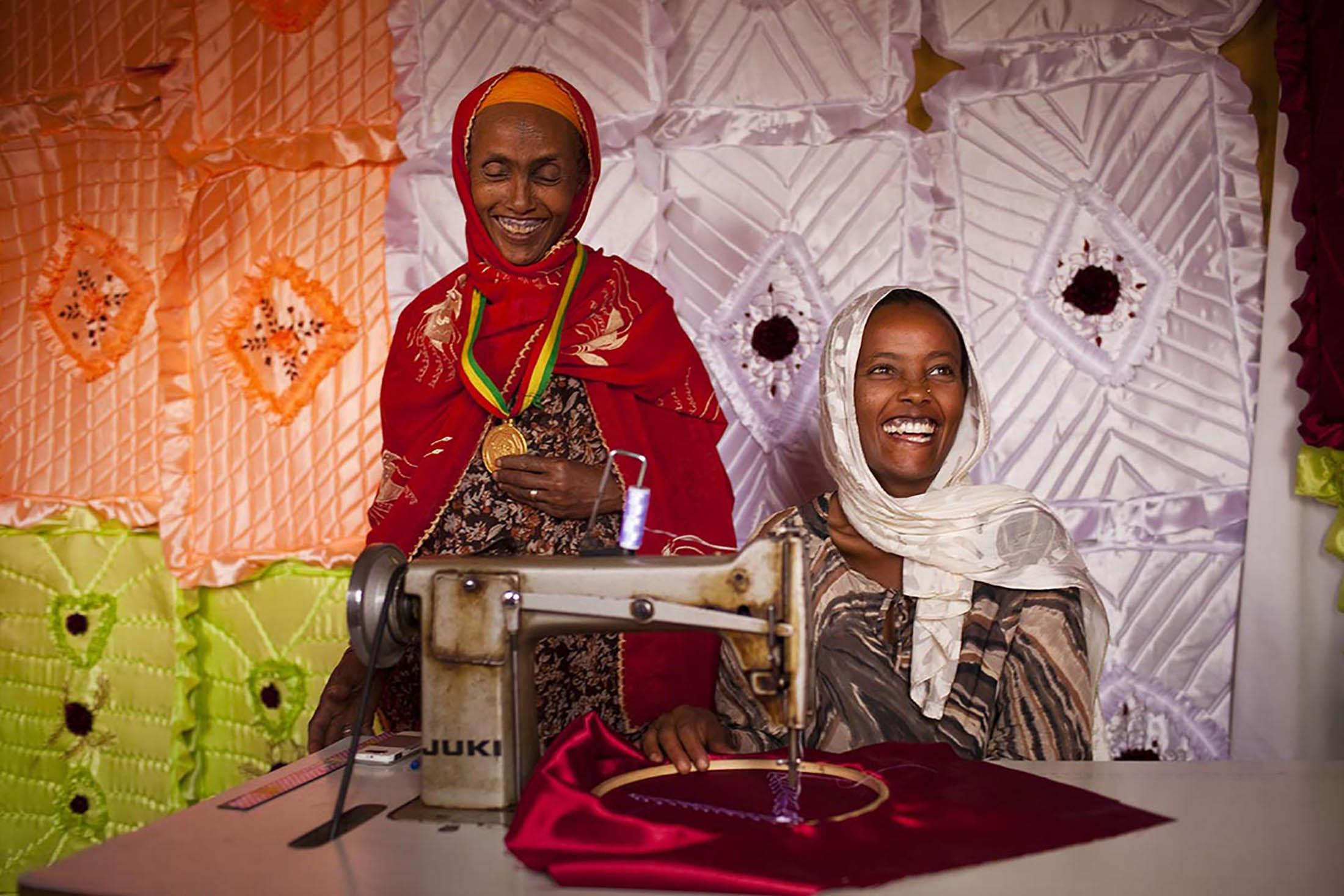 Triye Hussen, 35, at a sewing shop with her daughter Zeritu Hussen, 18, in Mender Village in Amhara region of Ethiopia, January 18, 2011. She participated in the Productive Safety Net Program (PSNP) by World Food Program (WFP) for 3 years, and won an award for her strong participation in PSNP in 2009 . The divorced mother said that her land was degraded because she did not know how to care for it. With the help of PSNP, she started using compost and new planting strategies to maintain earth fertility. After production increased, she managed to sell the seeds from her excess crops to a cooperative. With the new income, she bought livestock and two sewing machines which her daughter uses to run a sewing shop.
