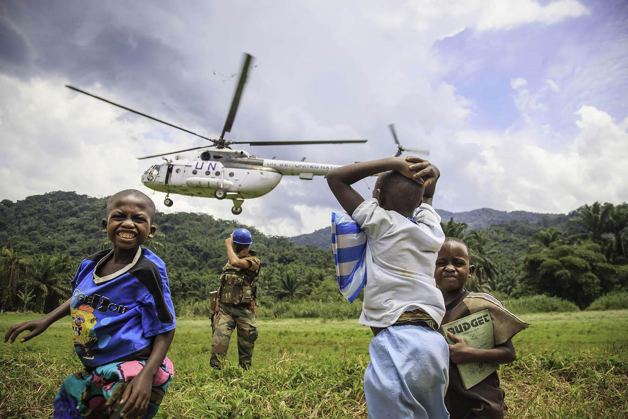 Children look on UN peacekeepers arrive in the area controlled by an armed group in North Kivu, Democratic Republic of Congo.