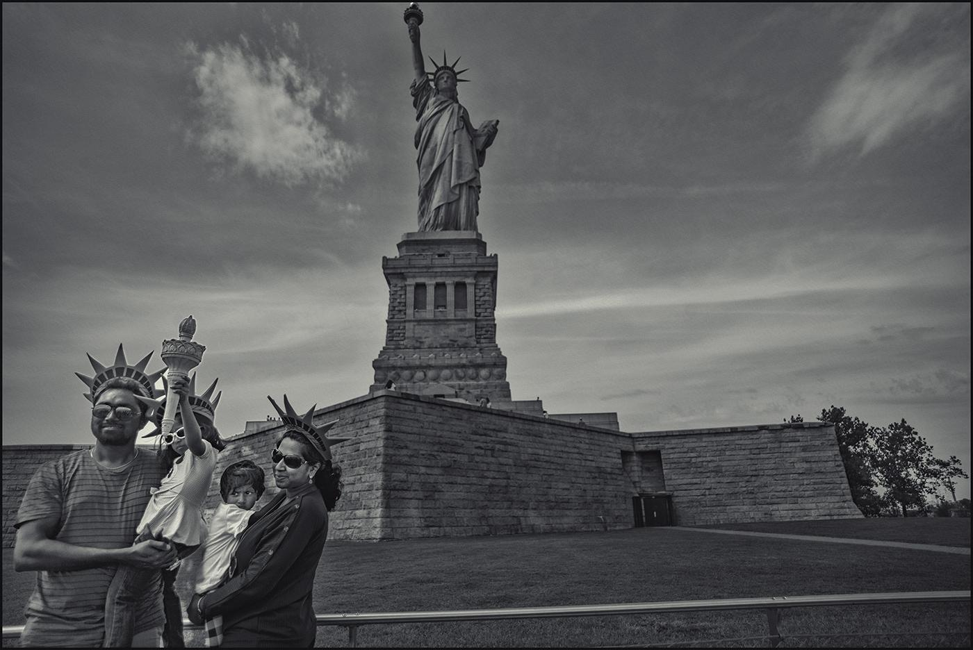 "The real ""Lady Liberty"" stands high above South Asian family. Statue of Liberty National Park, NYC.August 2019."