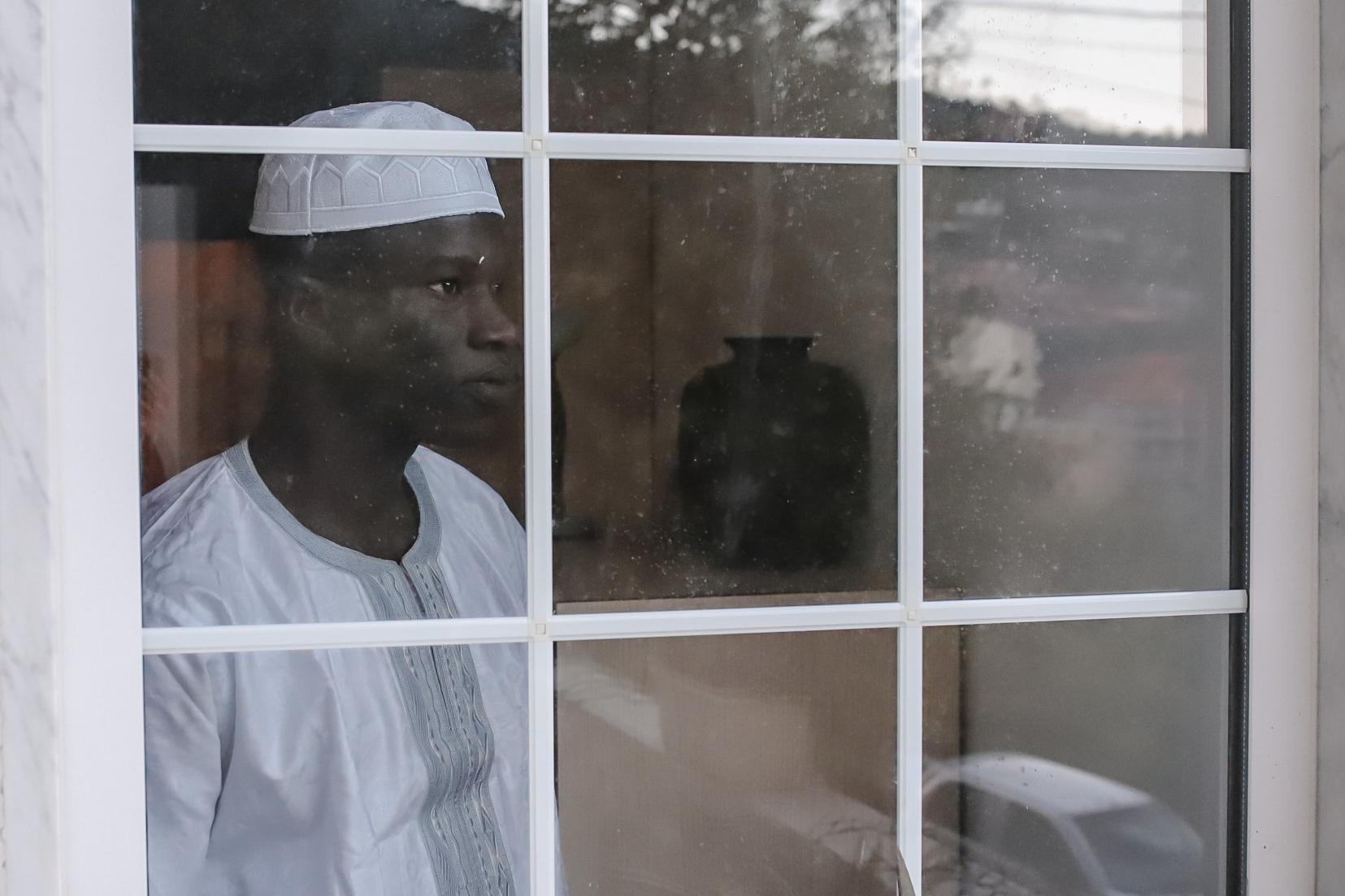 A refugees looks through the window of a residential NGO appartment in Amelia (Italy)