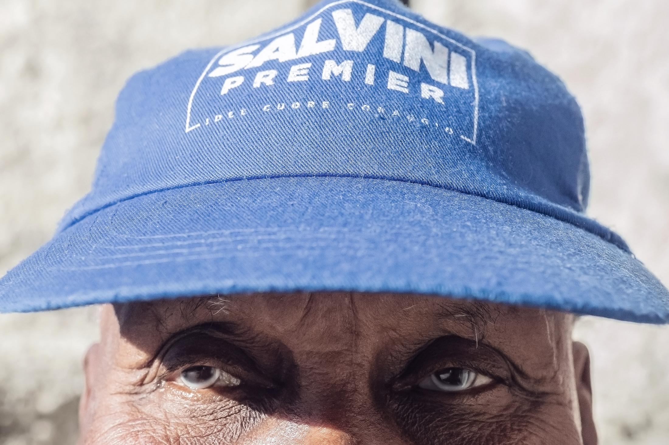 A man from Somalia is wearing a Salvini premier hat (Italy)