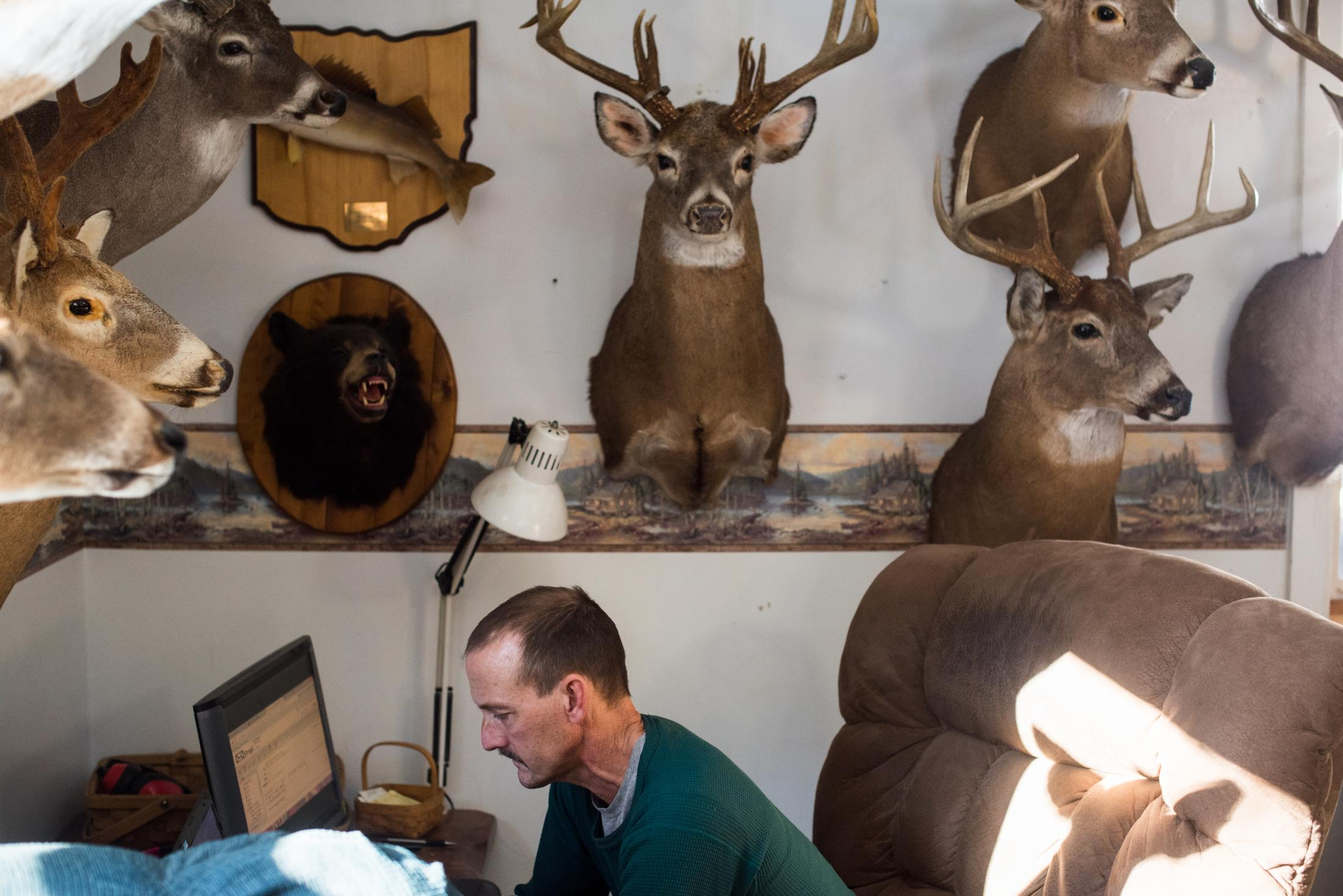 Dave Rupe types on his computer beneath his collection of deer mounts at his home two miles outside the center of the village of Coolville, Ohio, in February 2015. Rupe, who has lived in the area his whole life, is a skilled craftsman and makes a living by both selling his wares and by finding and reselling online items ranging from old farm equipment to unwanted animals mounts.