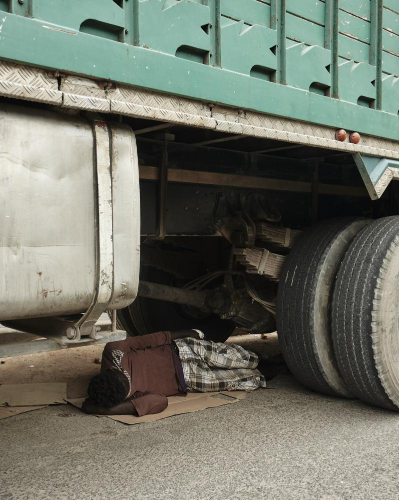 A young man sleeps under a truck in the streets of Casablanca.