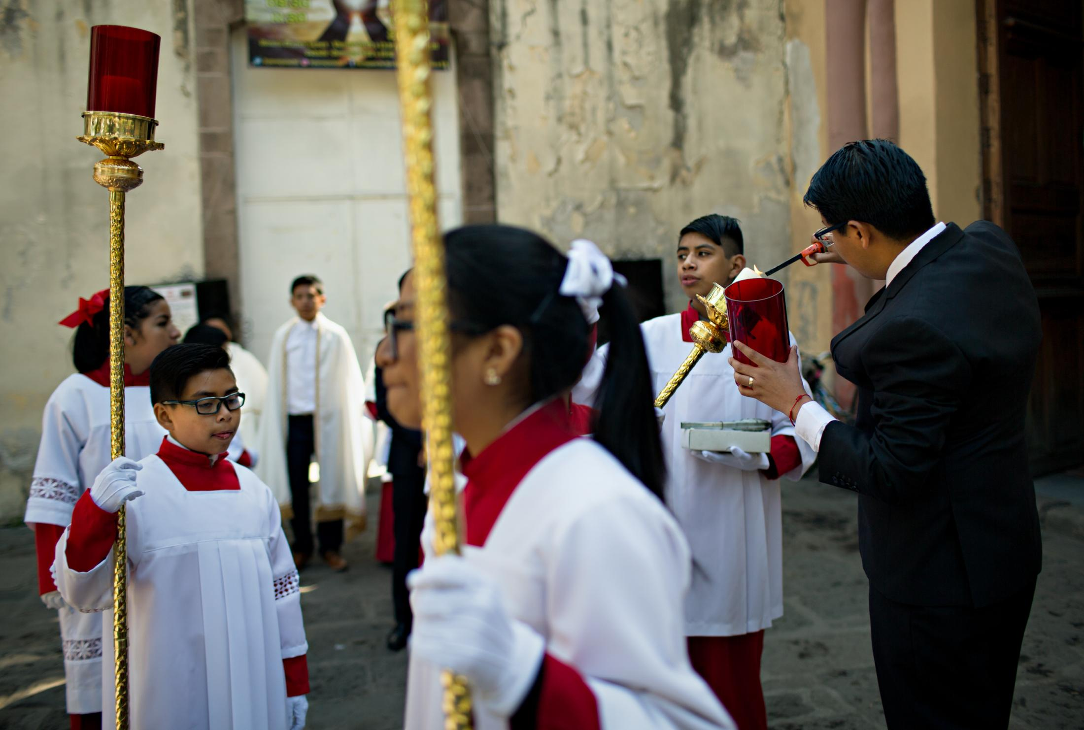 At the cathedral, alter boys and girls wait for the arrival of the Cardinal and the Niñopa.
