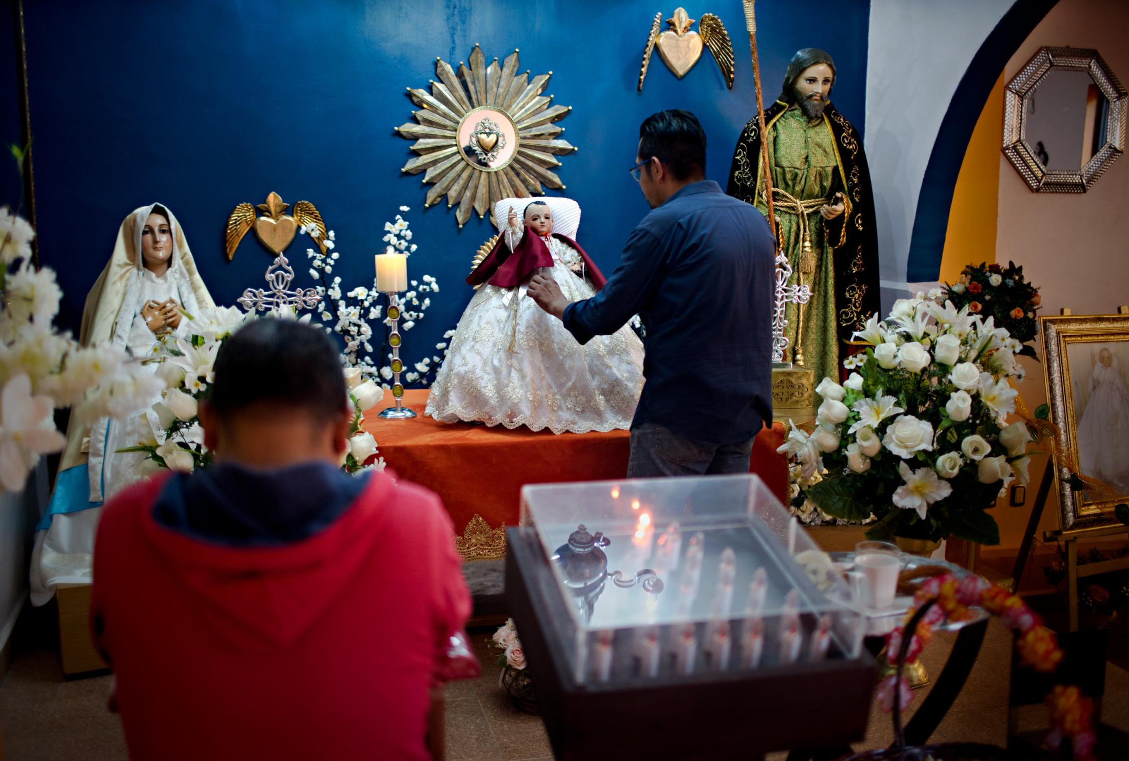 Jorge Serralte Huerte straightens Niñopa's dress in his living room which has been turned into a worship room for the year Niñopa will stay at his house. Fourteen years ago, when he remodeled the house, his anticipated the arrival of Niñopa in 2019 and built the house having in mind the needs of the Niño. Worshipers come early morning before heading onto work to see the Niño.
