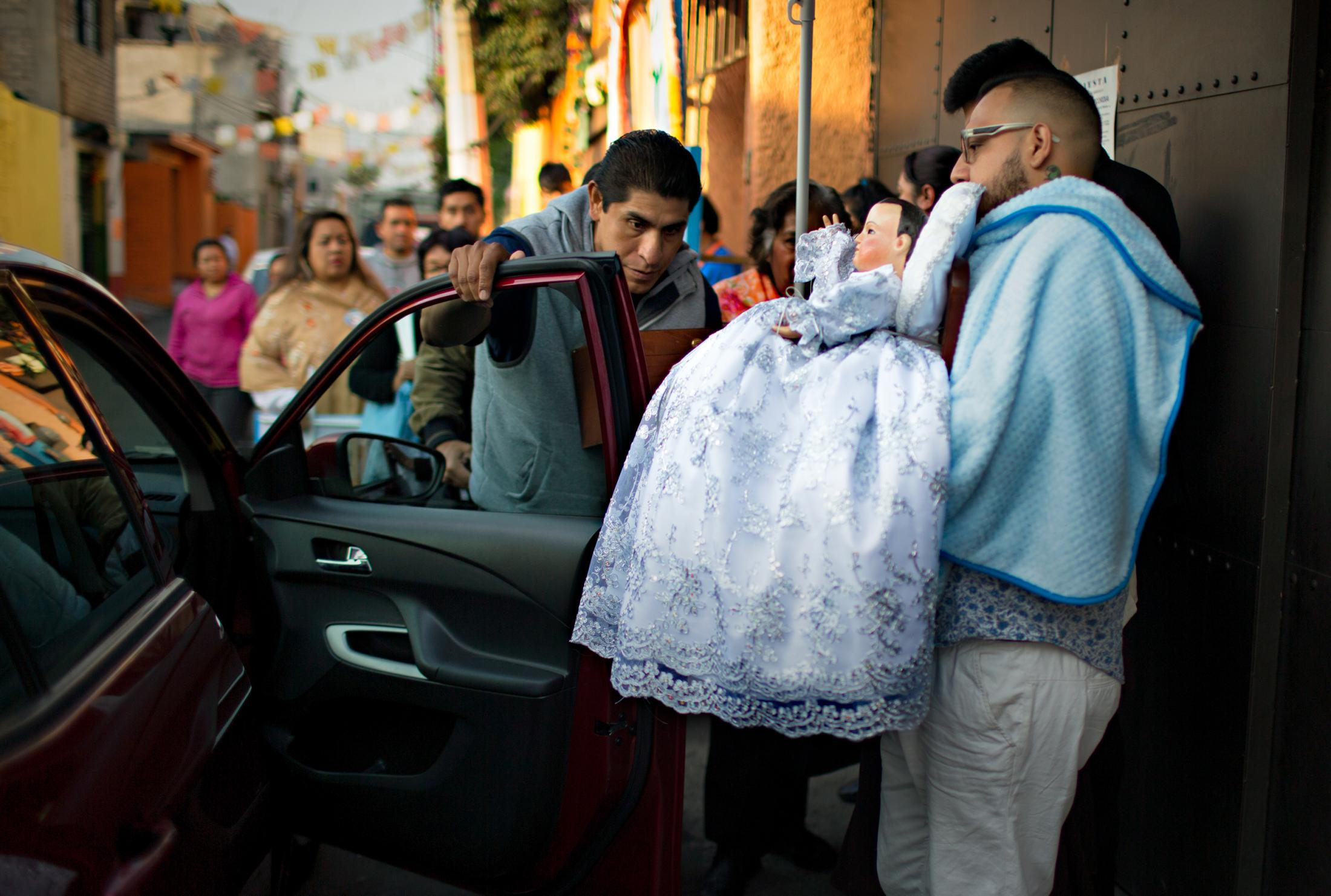 Neighbors take an active role in taking care of the Niñopa's needs. Here, friends and neighbors help the Niño getting into a vehicle to go visit a poor neighborhood about an hour away from Xochimilco.