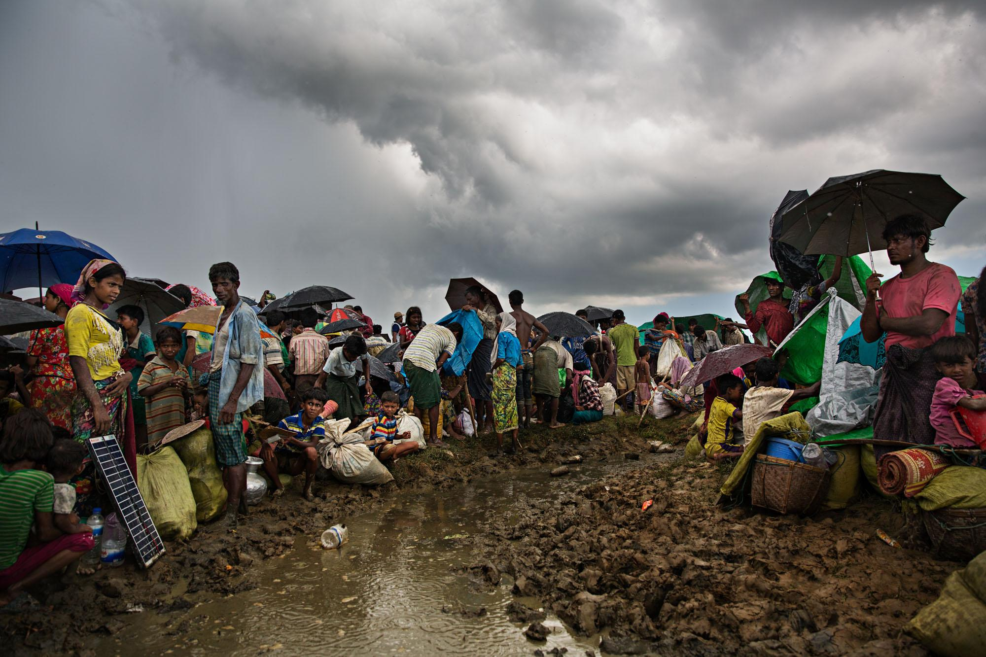Rohingya refugees huddle in a muddy field in a monsoon rain after crossing the Naf River from Myanmar into Bangladesh. Many of them walked for weeks to get here, some with gun or knife wounds, and had to wait all day and into the night in this field before being allowed into the camps in Cox's Bazar.