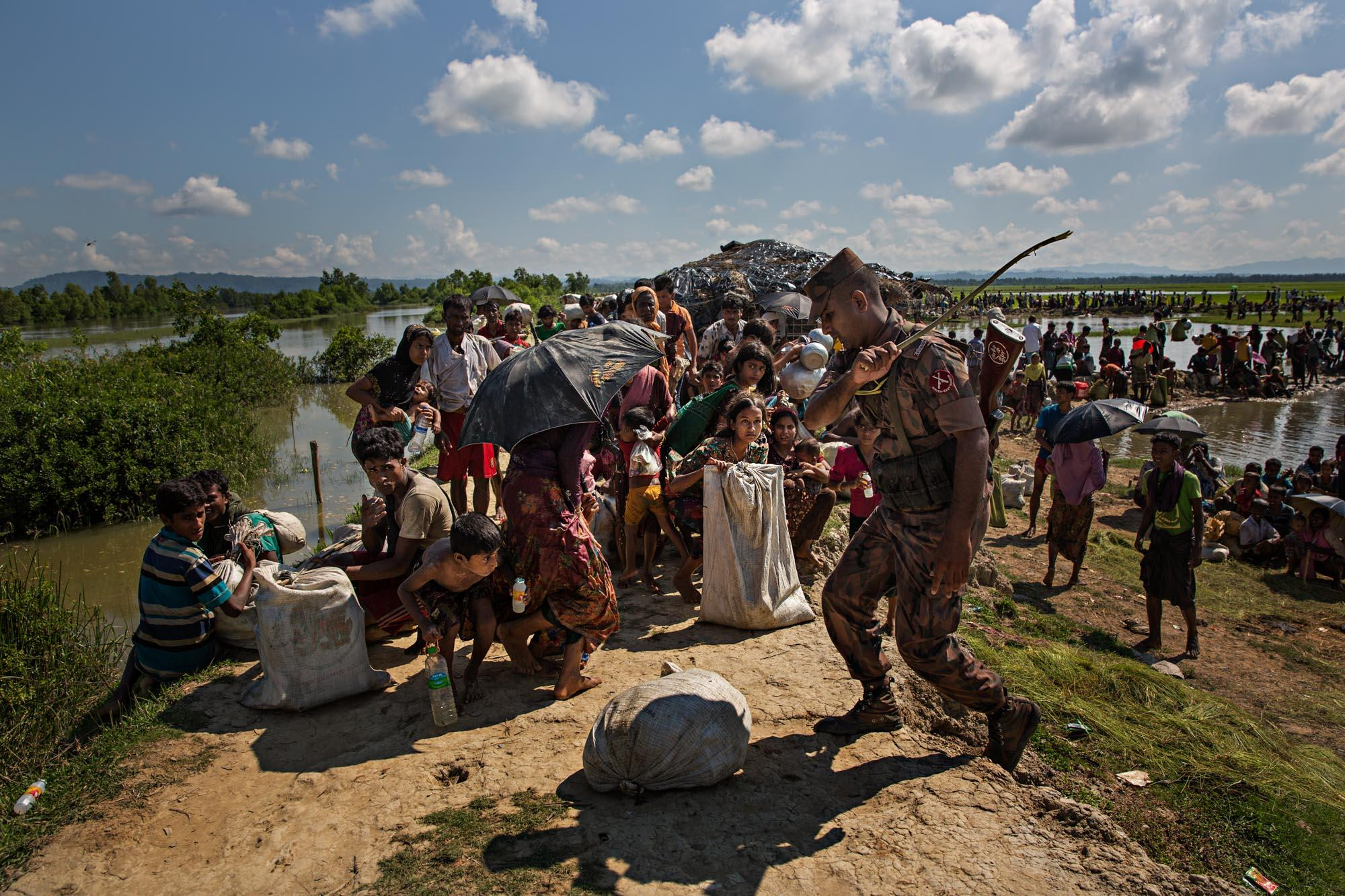 A Boarder Guard Bangladesh (BGB) officer swats at Rohingya refugees with a stick to keep them from going any further in an attempt to control the tide of people coming across the Naf River from Myanmar into Bangladesh.
