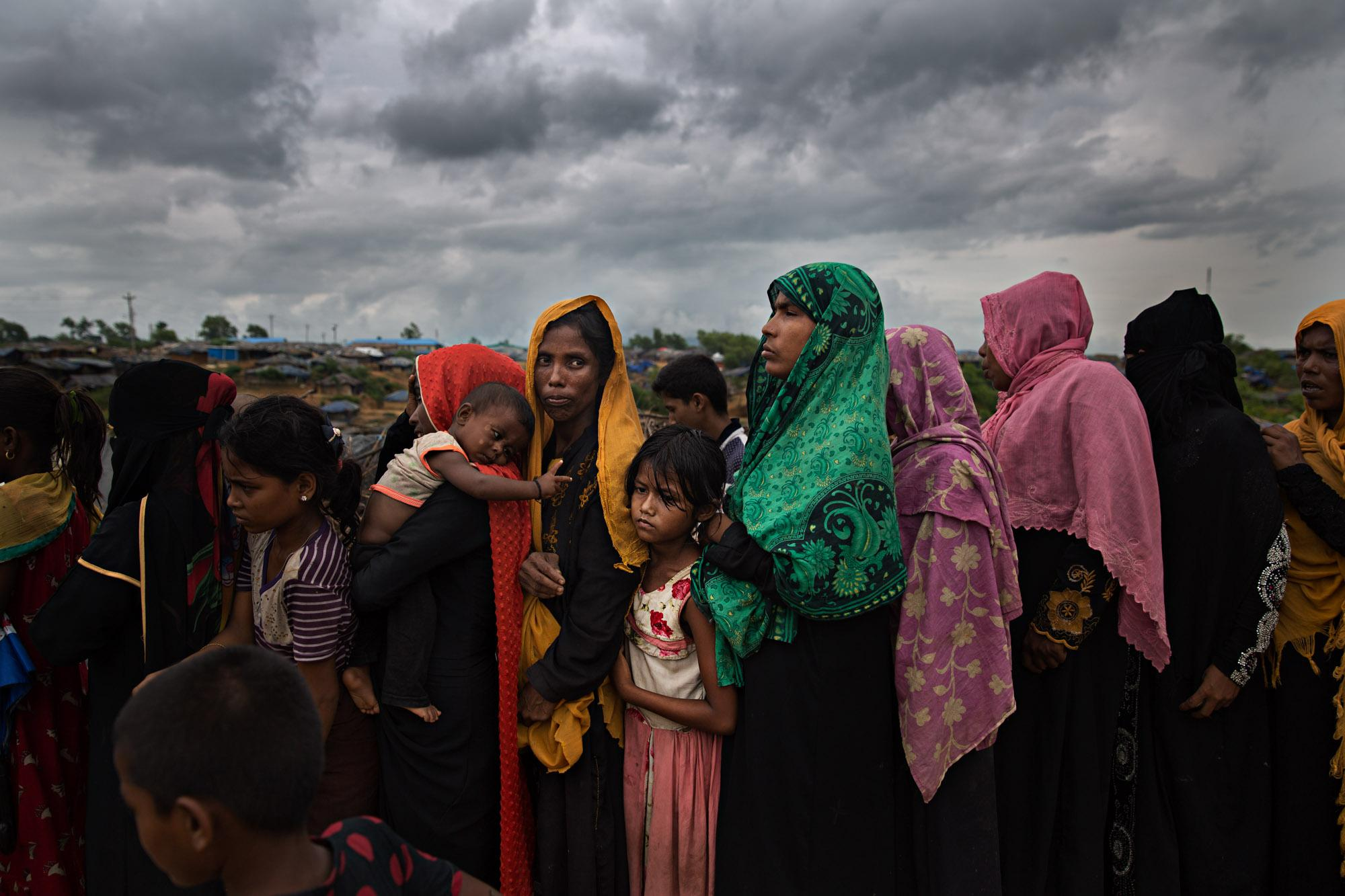 Rohingya women and girls wait in a food distribution line in a camp outside Cox's Bazar in Bangladesh.