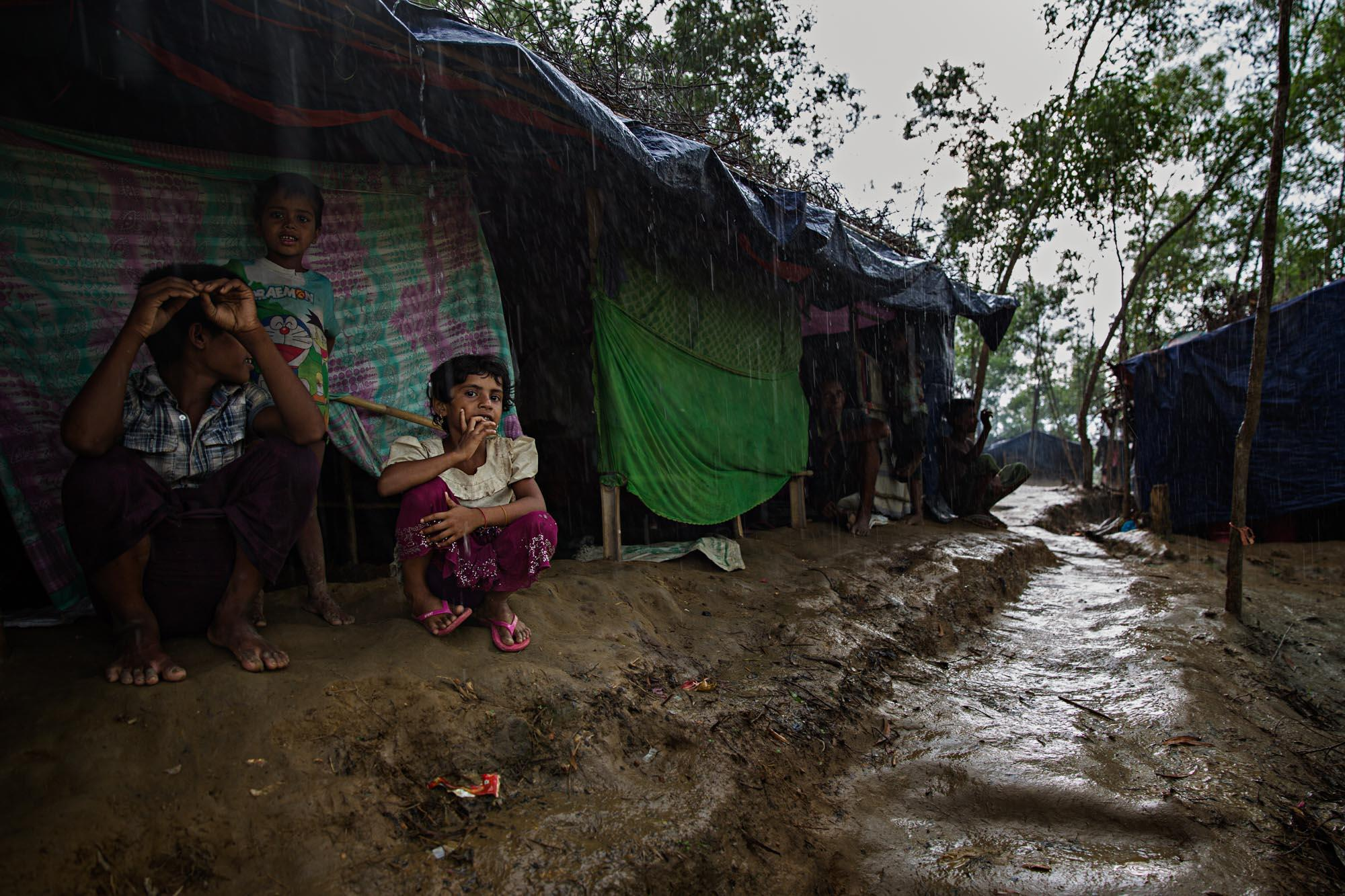 A young Rohingya girl waits out a monsoon rain in a camp outside of Cox's Bazar, Bangladesh. The heavy rains turned the hills into slippery, muddy slides and the valleys into ponds. Every inch of land had to be cleared quickly and the rainy season created slippery hills, lots of mud and poor sanitation.