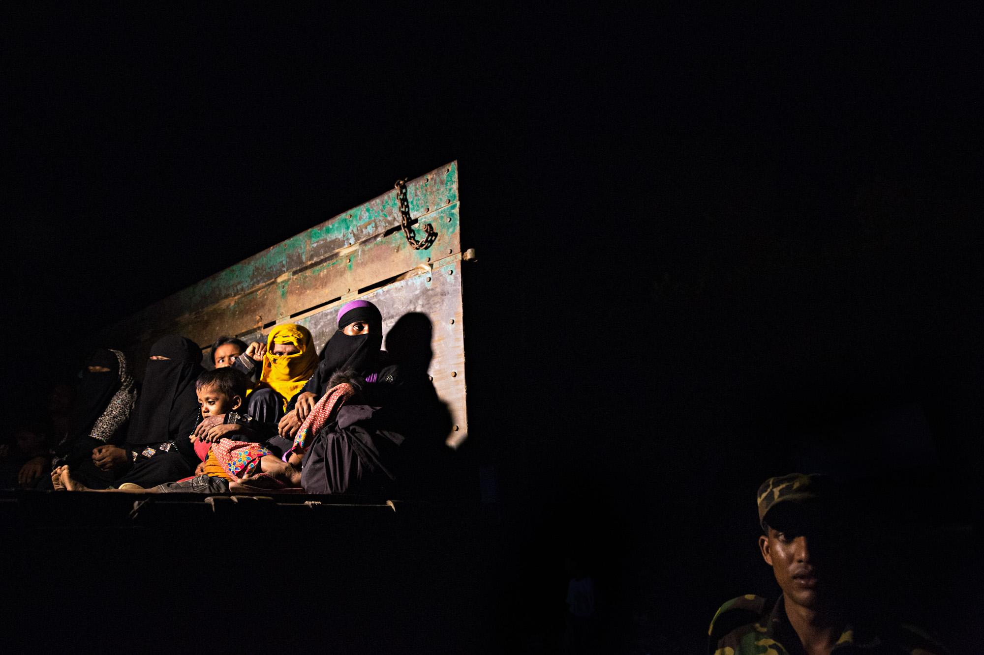 Rohingya refugees are loaded into a truck late at night for transportation to the camps outside of Cox's Bazar, Bangladesh.