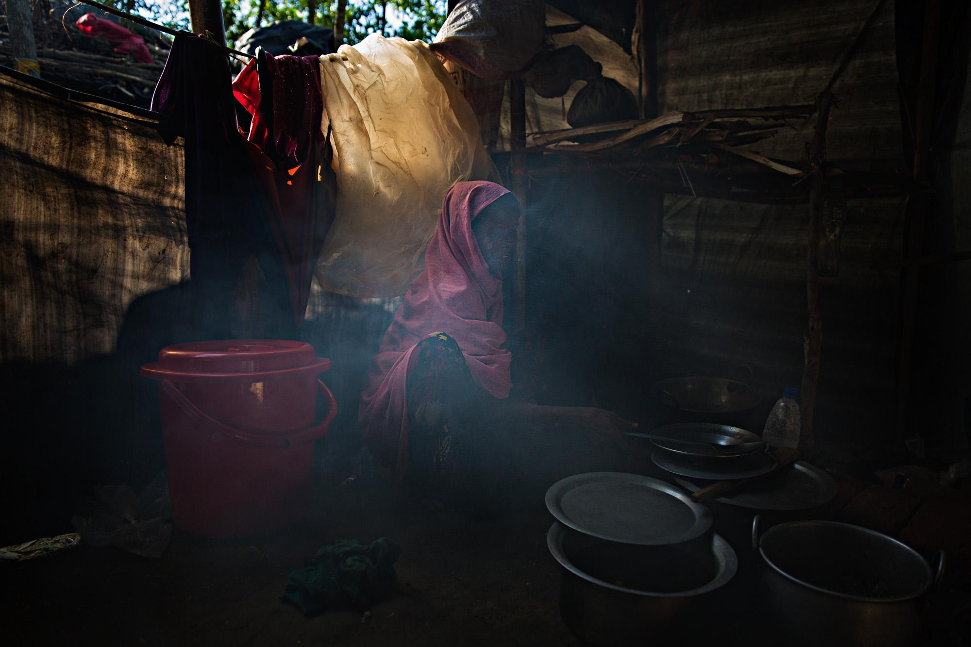 A Rohingya woman cooks in her hut in a camp outside of Cox's Bazar, Bangladesh.