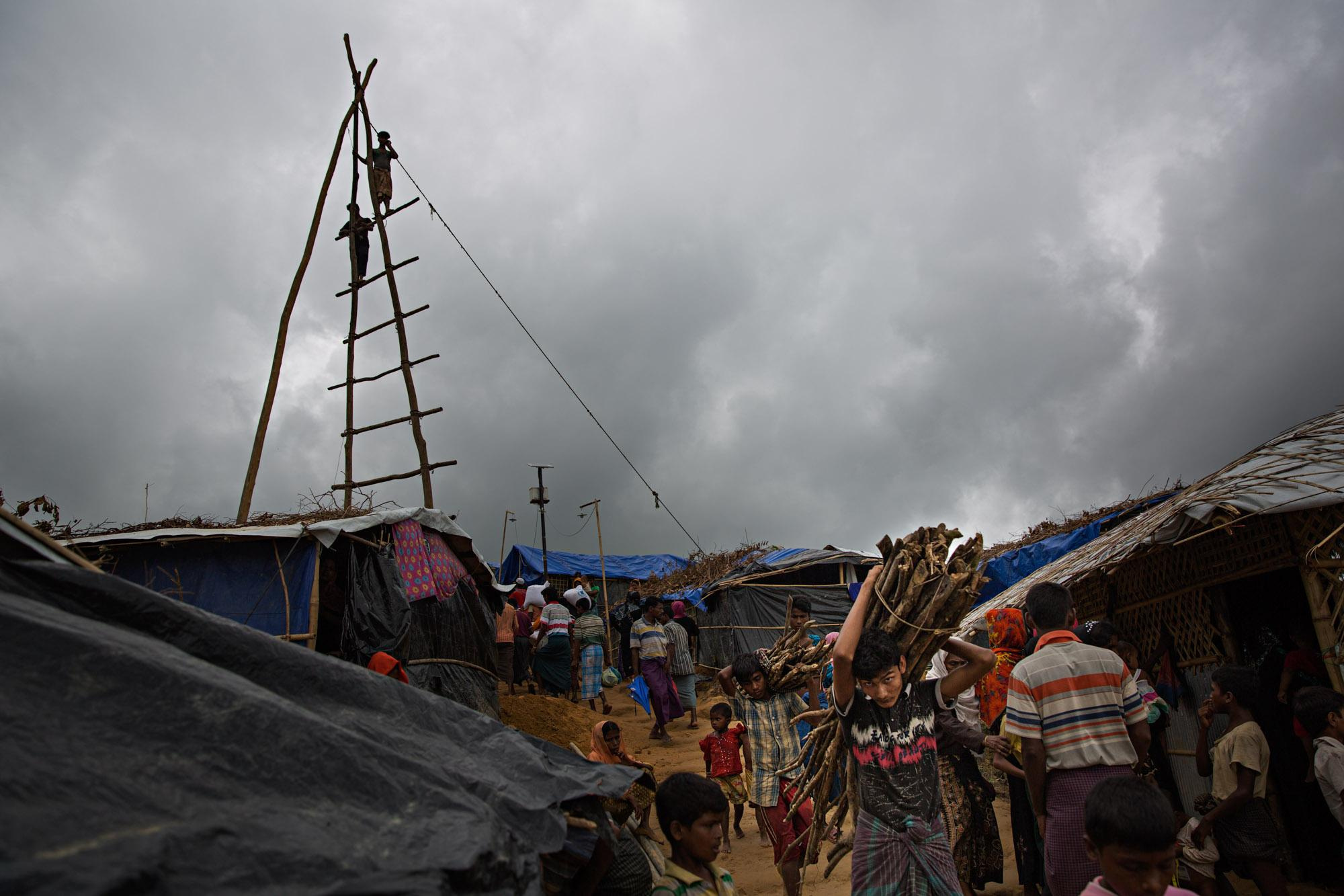 Rohingya refugees move through one of the camps outside of Cox's Bazar, Bangladesh. In the distance the frame for a drill can be seen that will be used to make a water well.