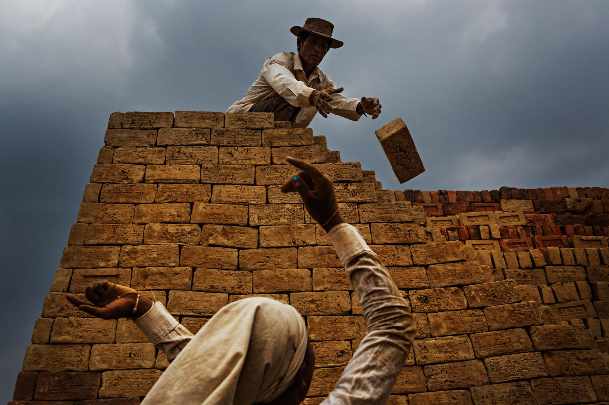 A father-daughter team tosses bricks to each other to build a small kiln on the outskirts of Yangon, Myanmar.