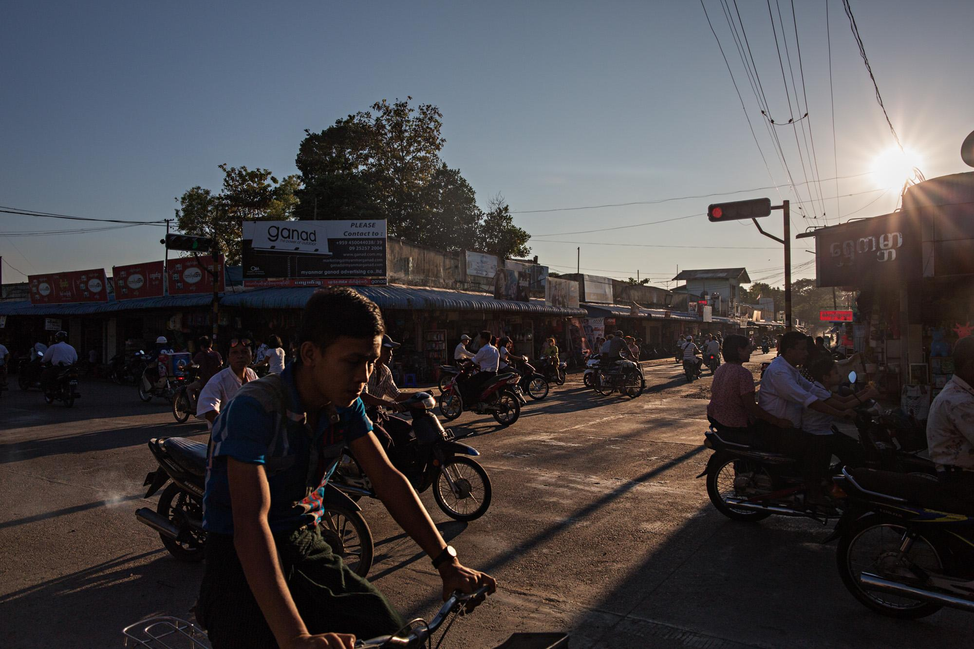 Cyclists and motorbikes make their way through the sleepy town of Hinthada, Myanmar.
